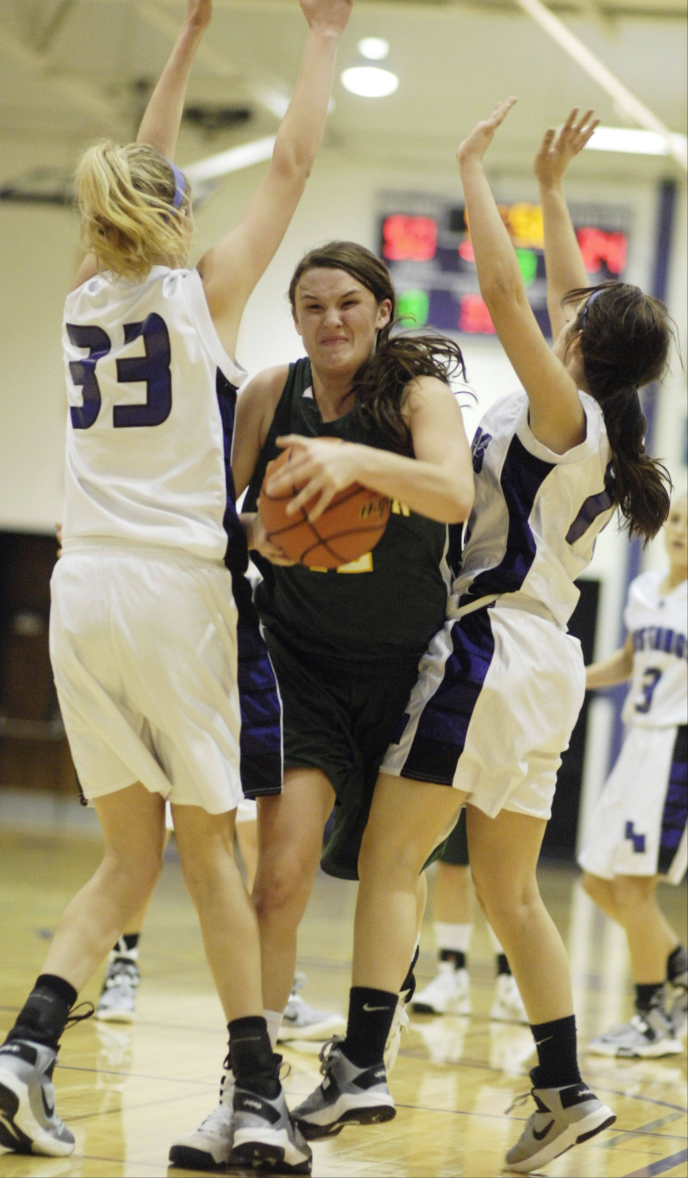 Stevenson's Alex Elzinga, middle, tries to drive between Rolling Meadows' Jenny Vliet, left, and Sami Kay during Tuesday's game.