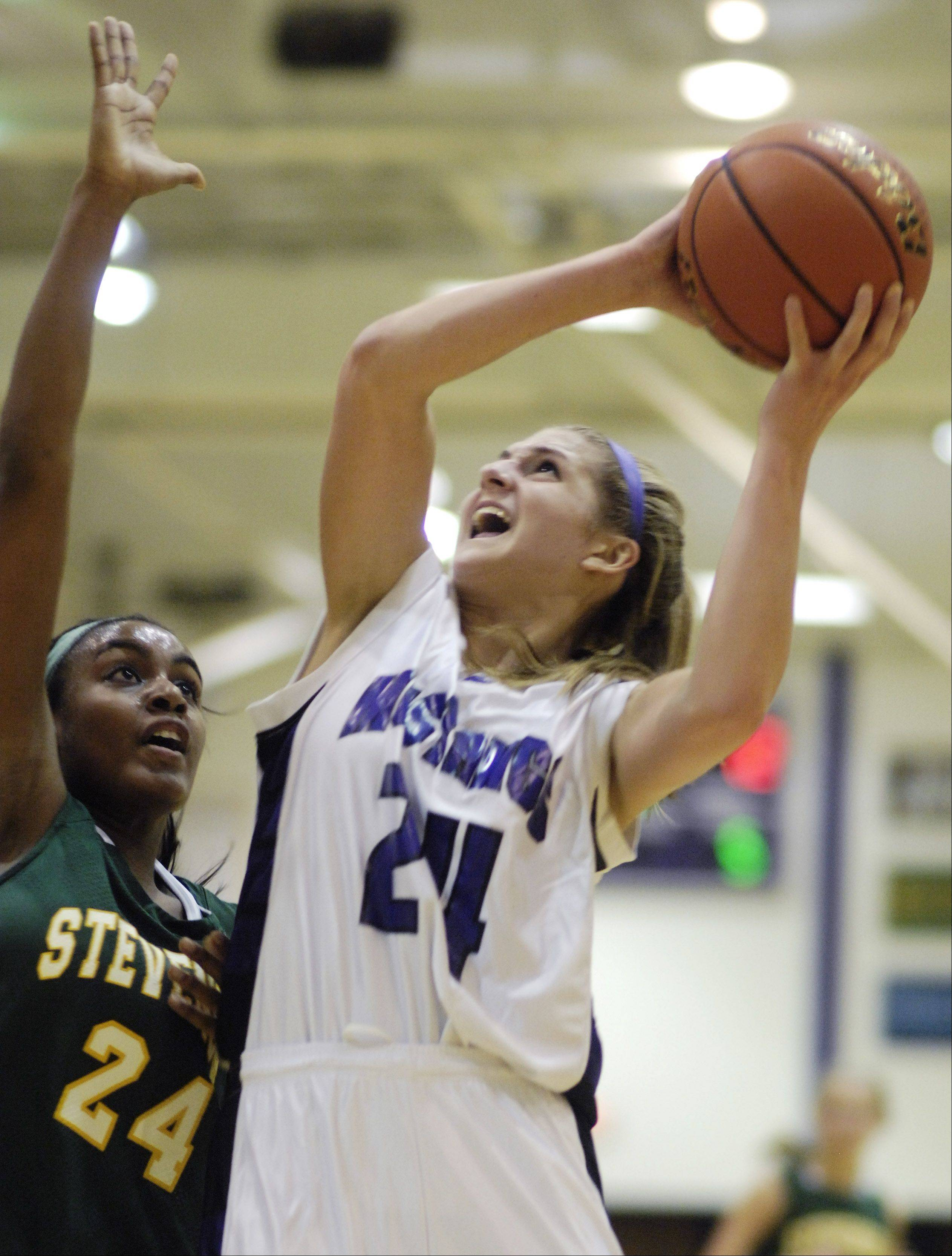 Rolling Meadows' Alexis Glasgow, right, takes a shot against the defense of Stevenson's Taylor Buford.