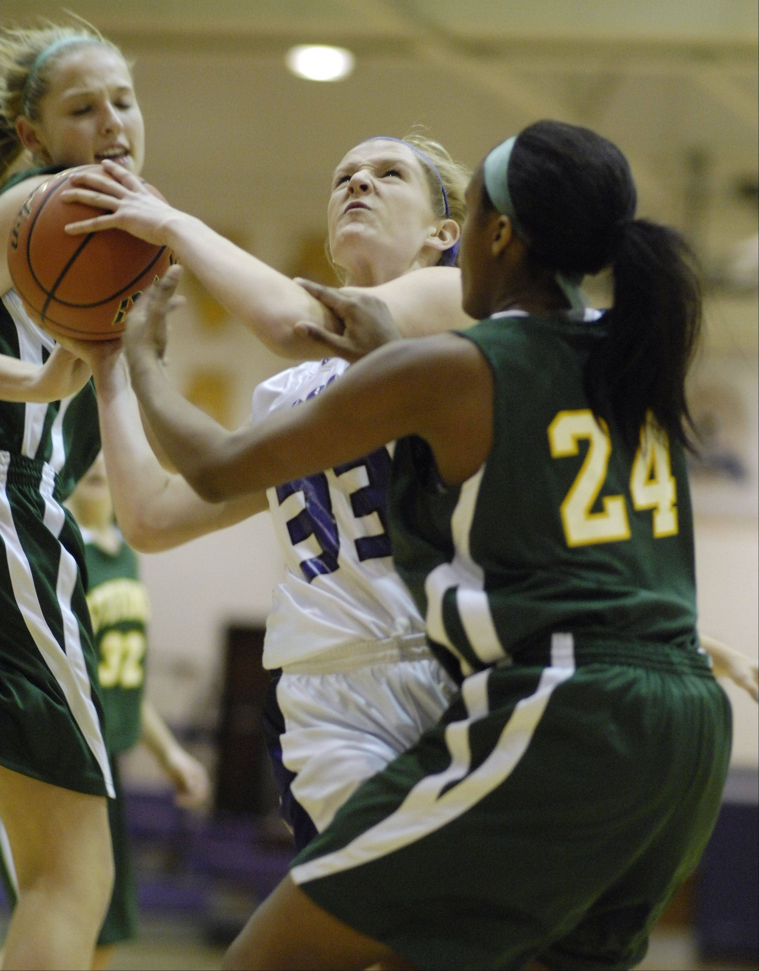 Rolling Meadows' Jenny Vliet, middle, drives to the basket against Stevenson defenders including Taylor Buford, right.