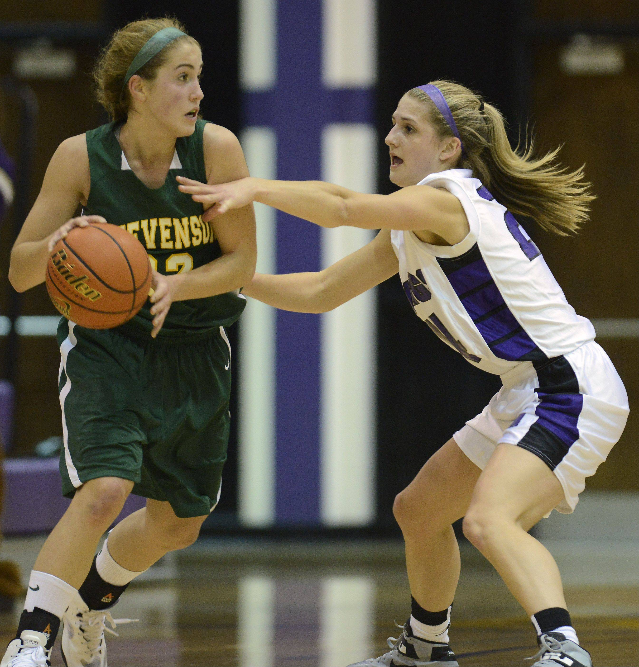 Stevenson's Sophia Way, left, looks for an open teammate while being guarded by Rolling Meadows defender Alexis Glasgow on Tuesday.