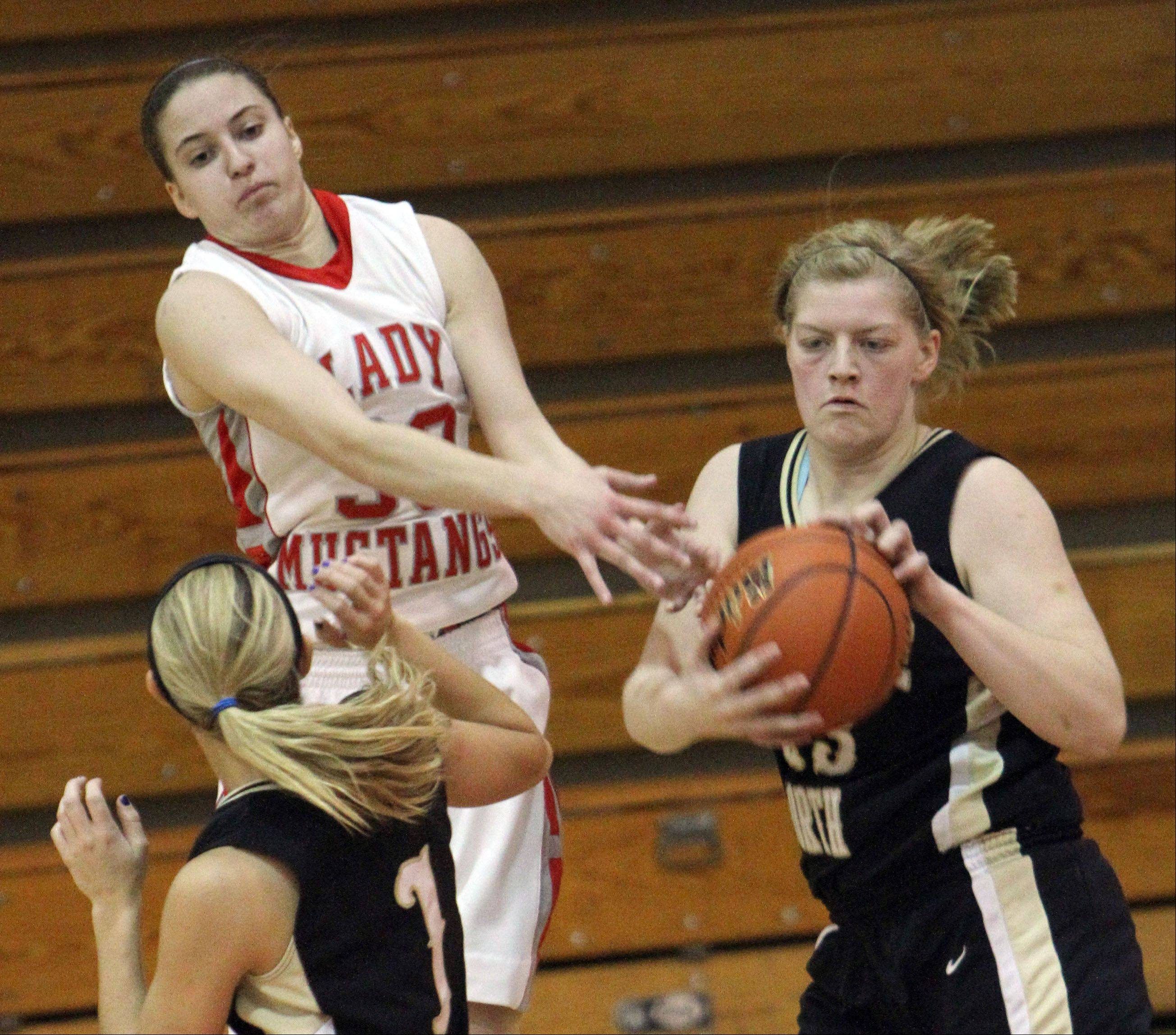 Mundelein's Lauren Rouse, left, battles for a rebound with Grayslake North's Joanna Guhl, right, and Jordyn Bowen during the Mundelein High School Turkey Tournament on Tuesday.