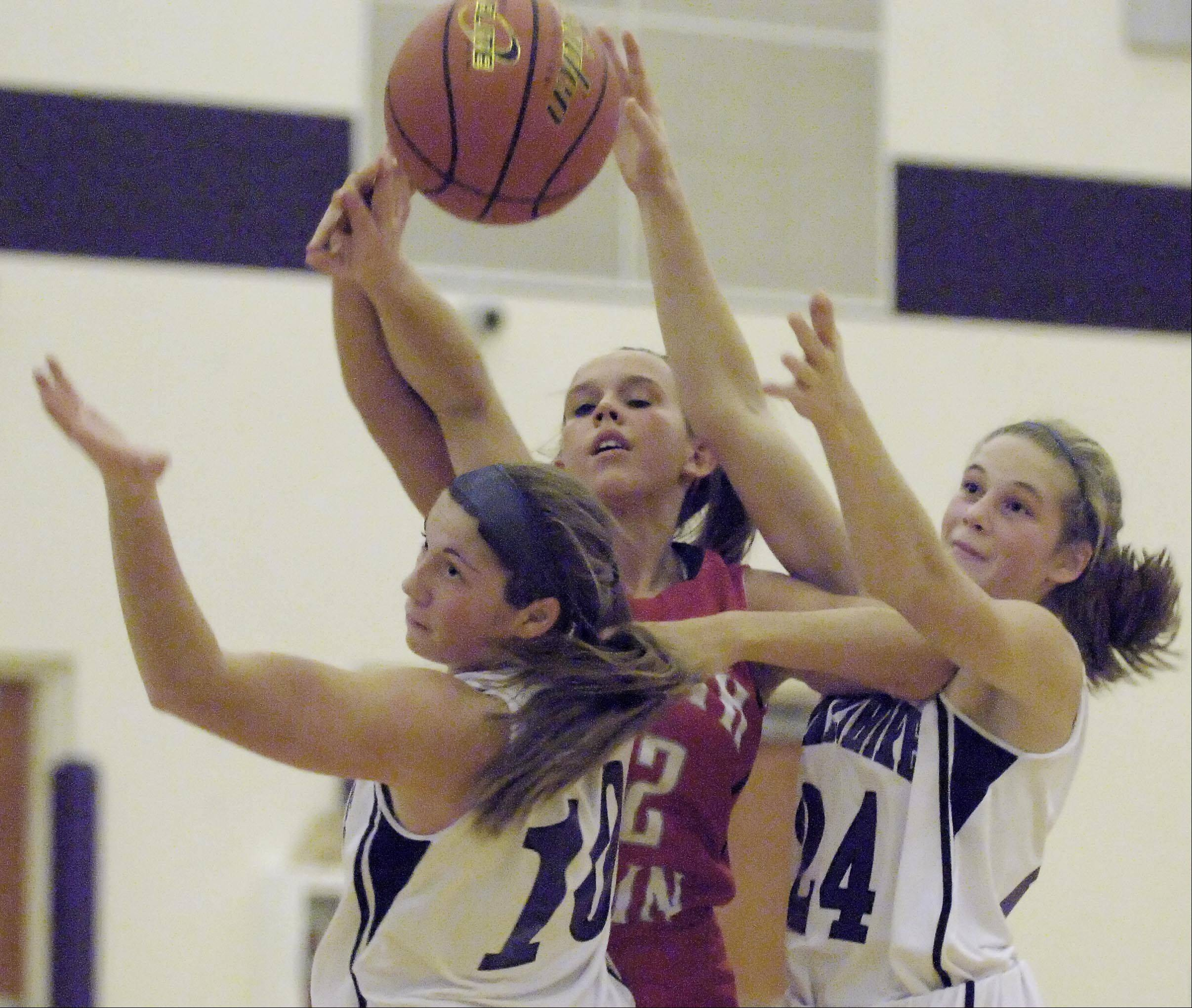 South Elgin's Laura McIntosh loses control of the ball under the defense of Hampshire's Jen Dumoulin and Nikki Dumoulin, right, late in the game Wednesday in Hampshire.