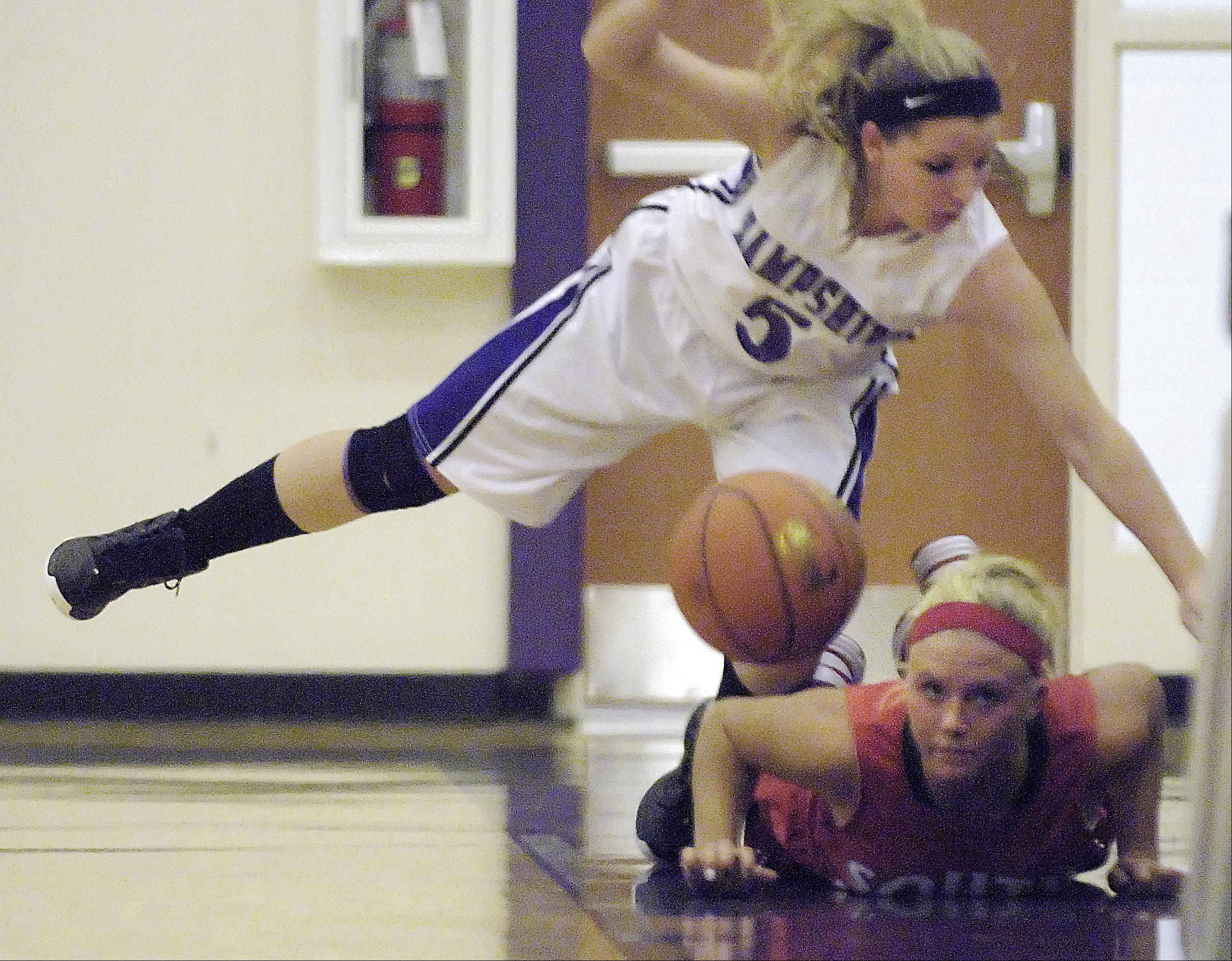 Hampshire's Claudia Lazar falls over South Elgin's Kara Rodriguez as they go out-of-bounds Wednesday in Hampshire.