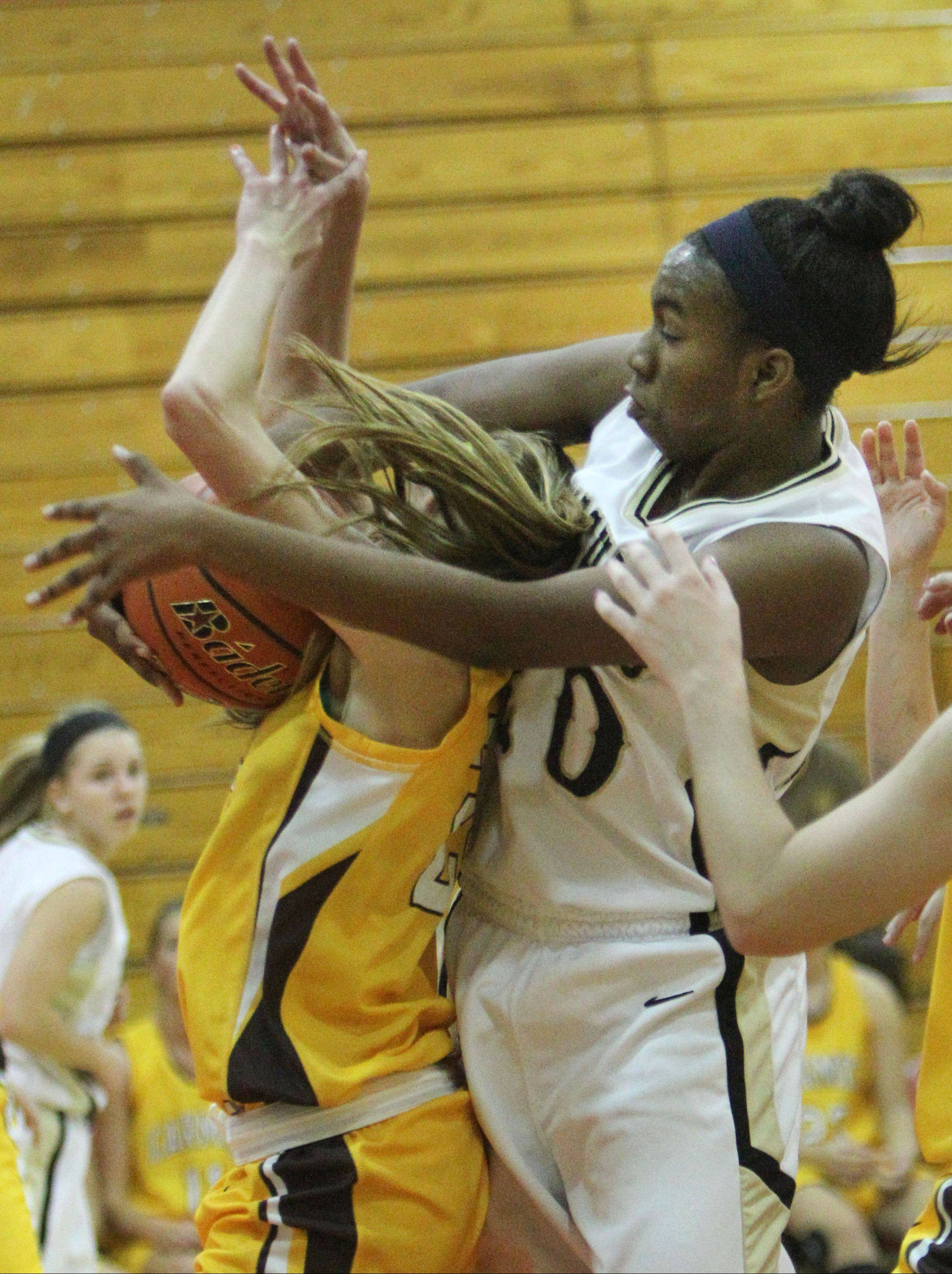 Grayslake North's Brittany Thibeaux, right, fights for a rebound with Carmel's Claire Ogrinc during the Mundelein High School Turkey Tournament on Wednesday.