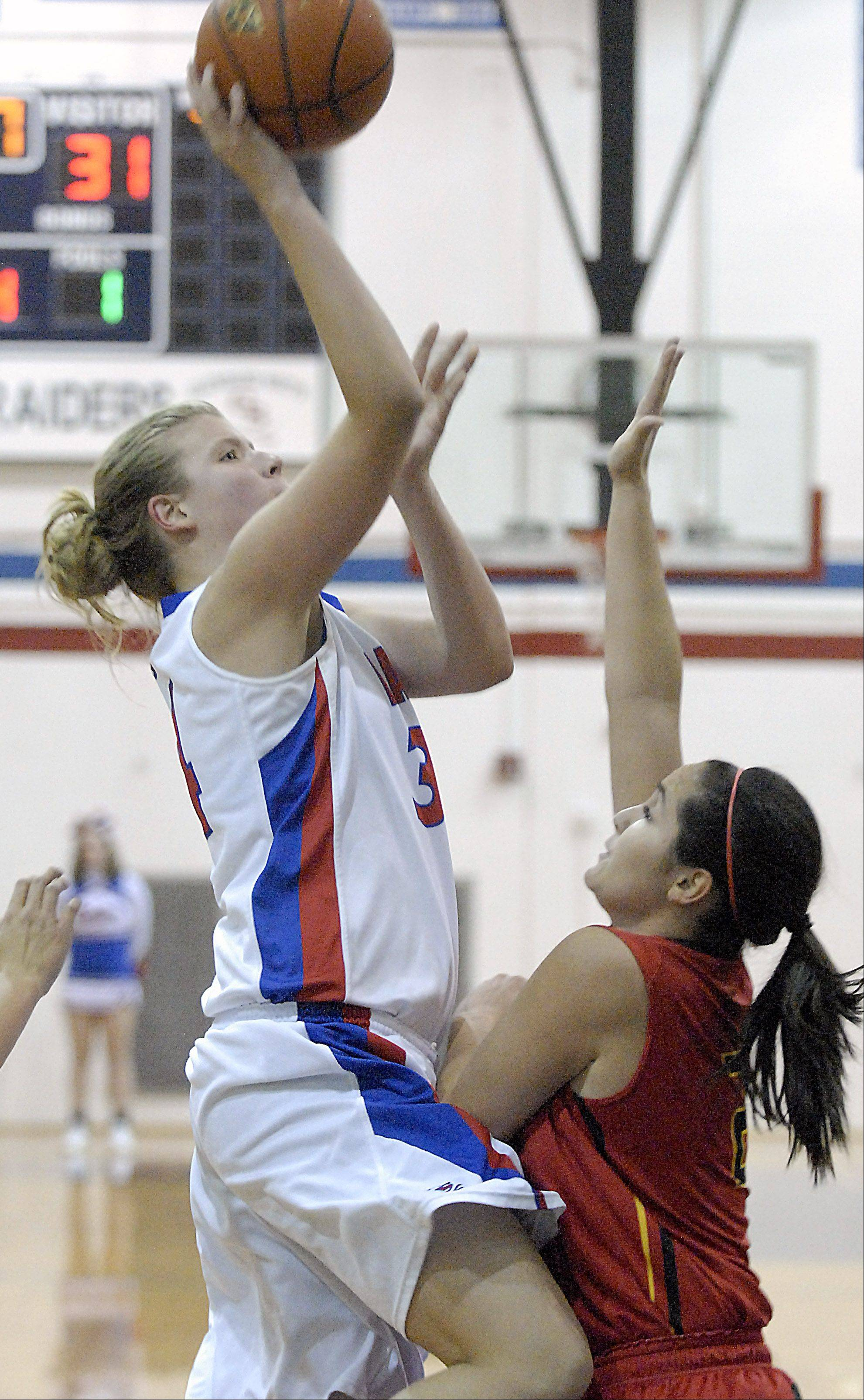 Glenbard South's Sydney Bauman shoots over Batavia's Sami Villarreal in the third quarter on Tuesday, November 13.