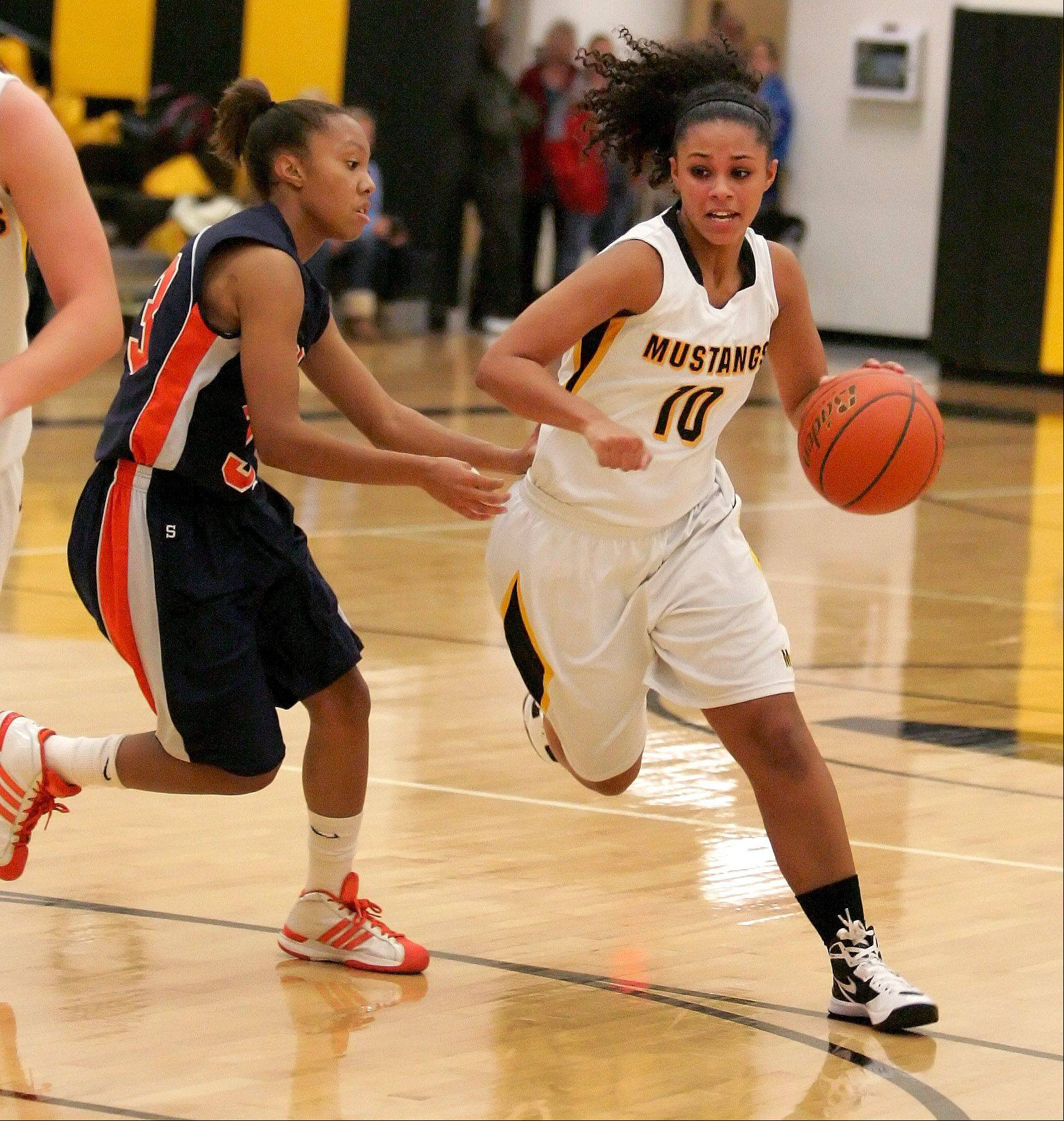 Bria Walker of Metea Valley drives around Zoe Swift of Naperville North, left, in girls basketball action on Tuesday in Aurora.