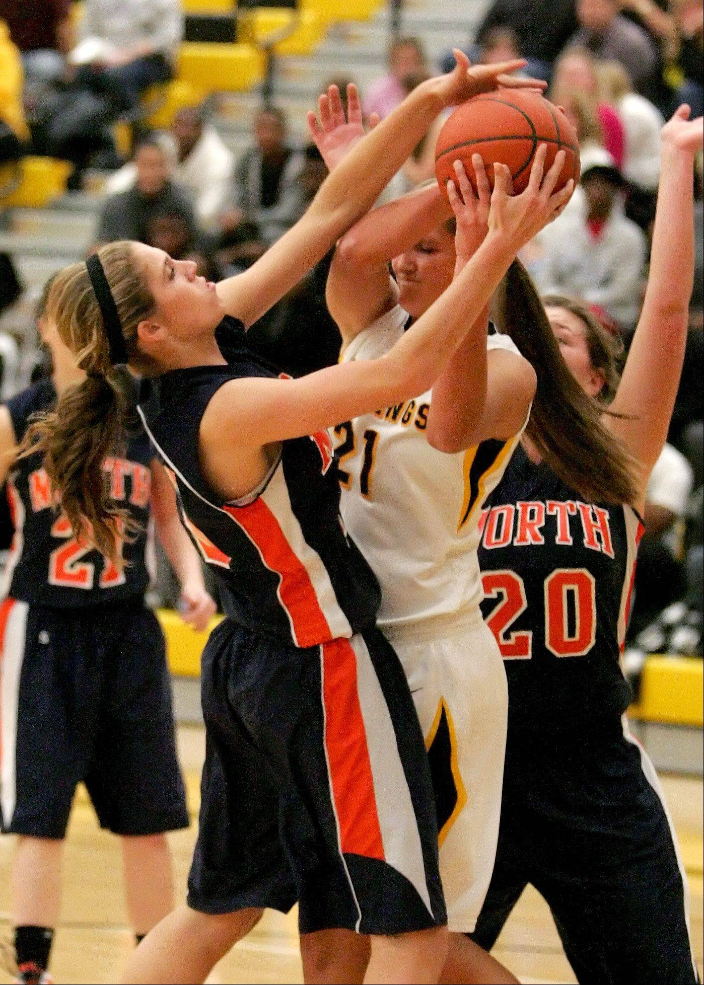 Kayla Sharples, left, of Naperville North and Anna Petersen of Metea Valley go up for a rebound in girls basketball action on Tuesday in Aurora.