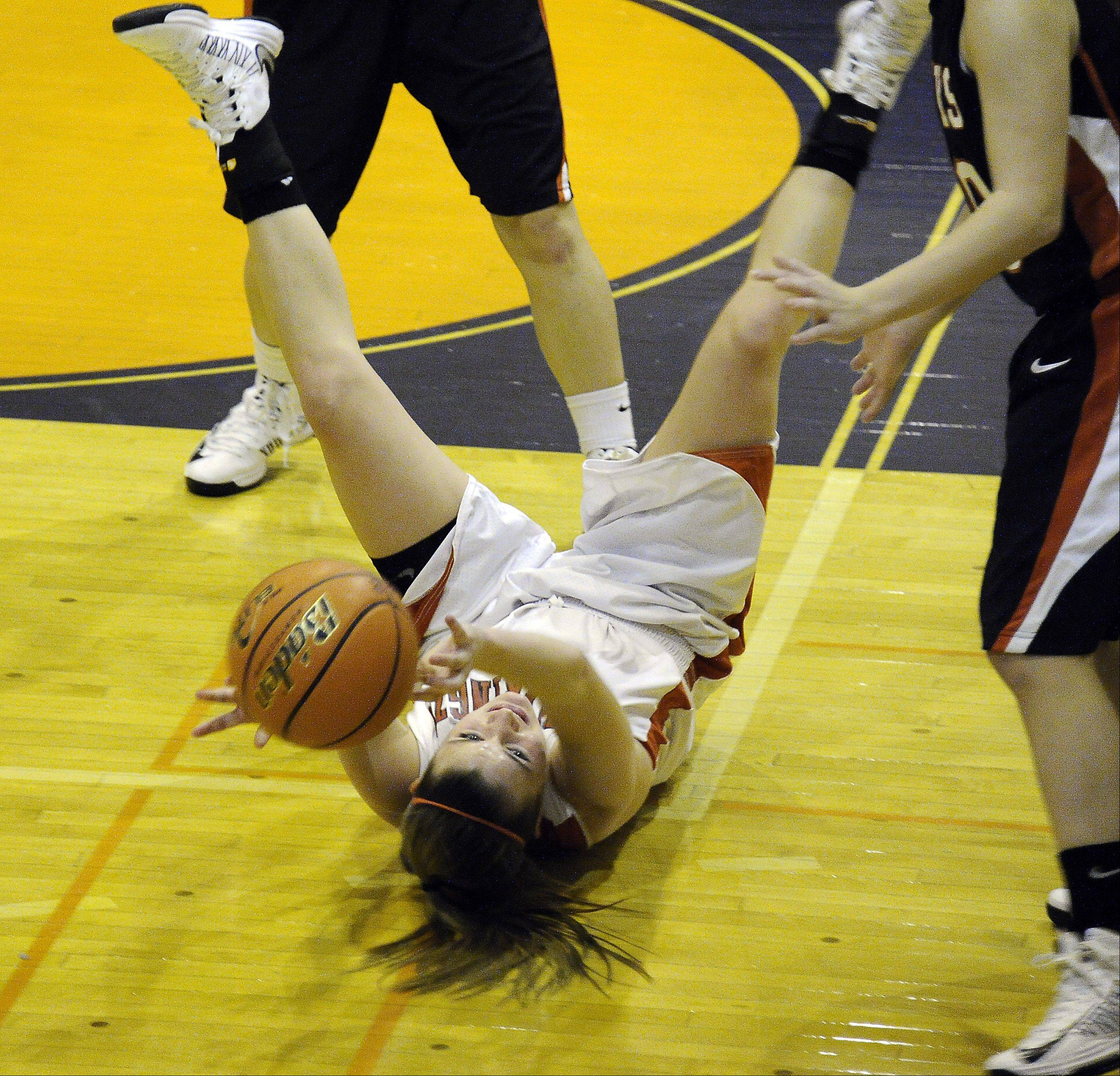 Barrington's Angie Kirchoff hits the floor but manages to pass to a teammate during the Bison Classic girls varsity basketball Thanksgiving Tournament at Buffalo Grove High School on Thursday.