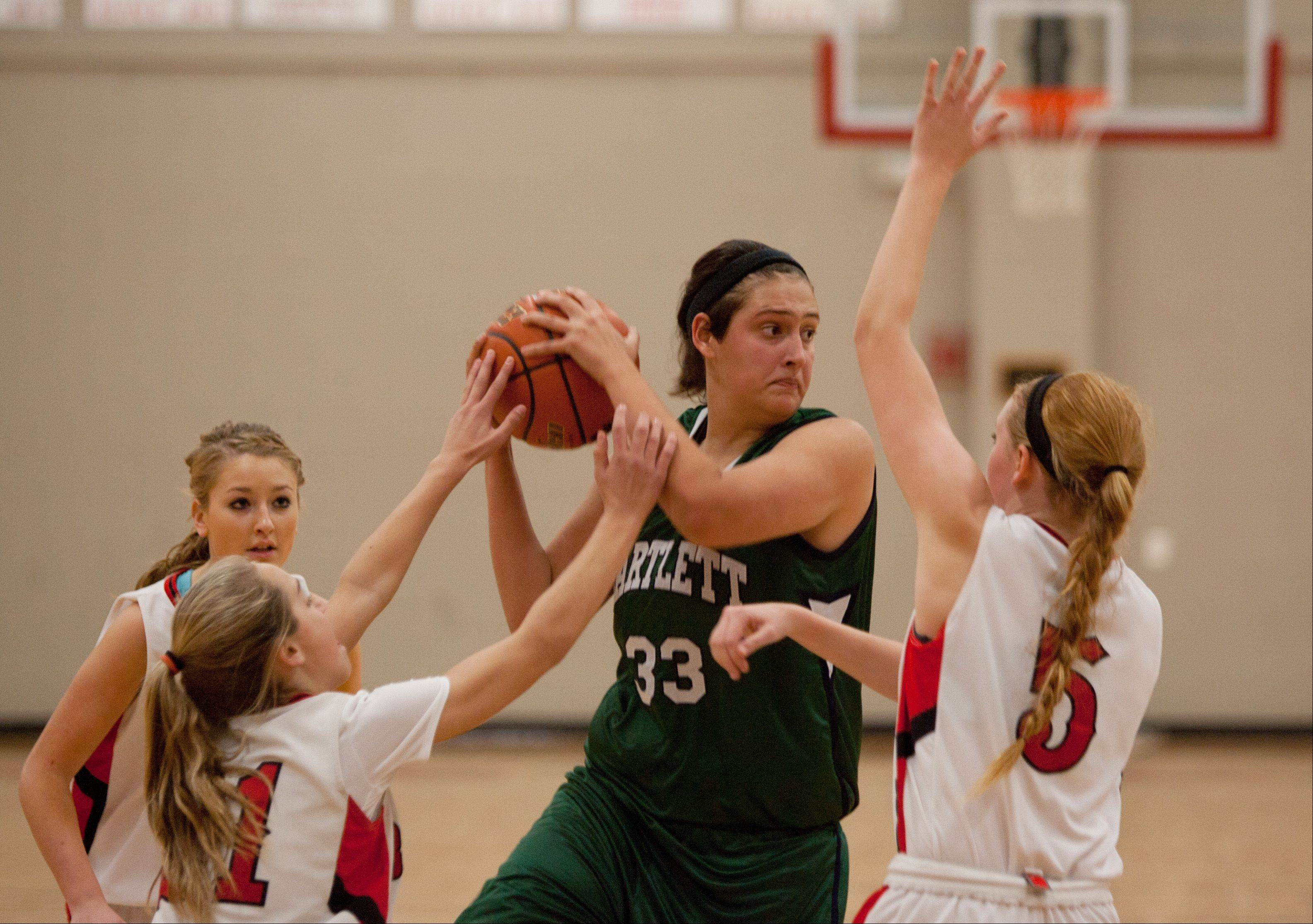 Bartlett's Alyssa Hernandez, center, battles Benet's Kathleen Doyle, left, and Jenna Martin, right, during girls basketball action at Benet,