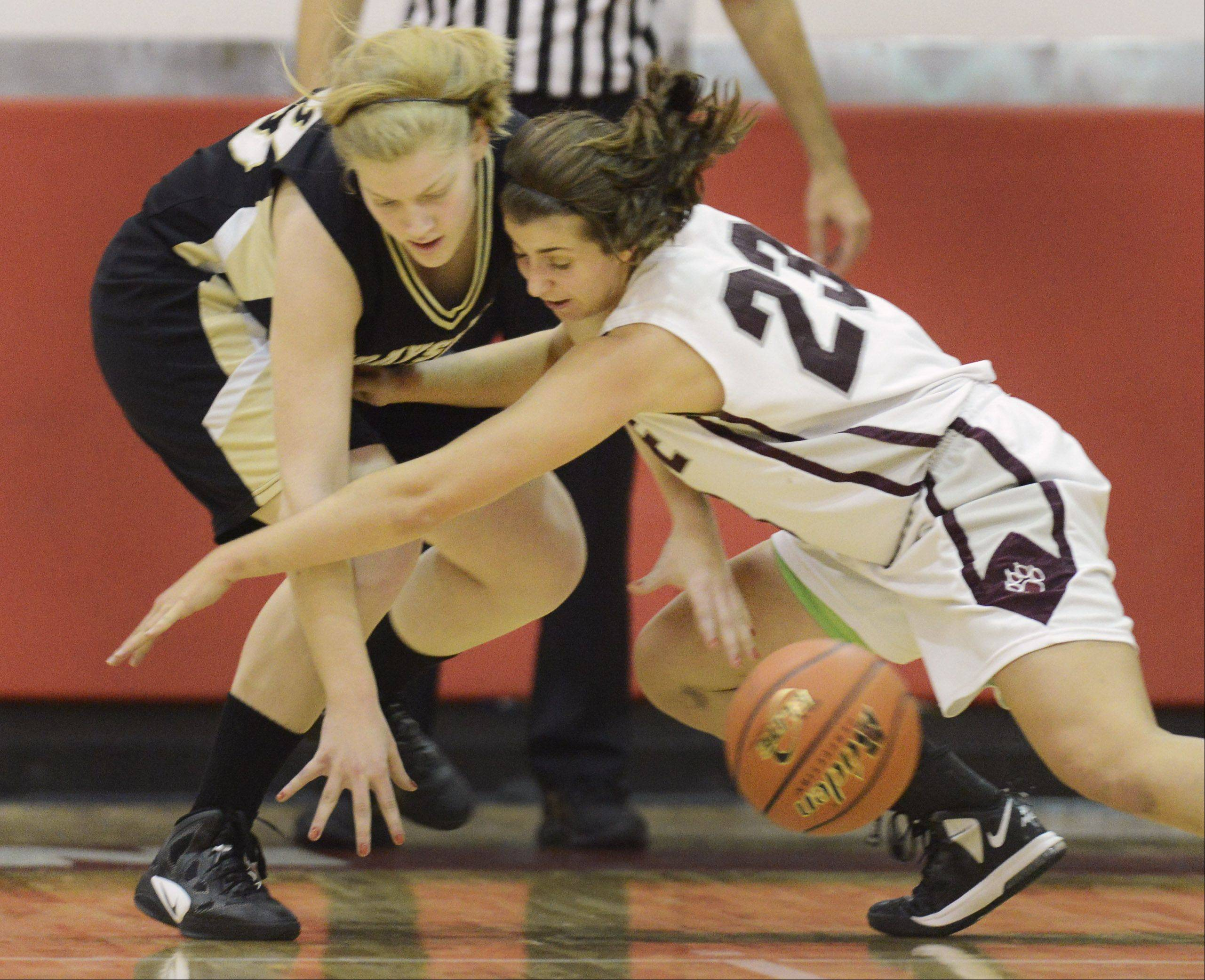 Joanna Guhl, left, of Grayslake North and Alex Neckopolous of Prairie Ridge try to control a loose ball during Friday's game at Mundelein.