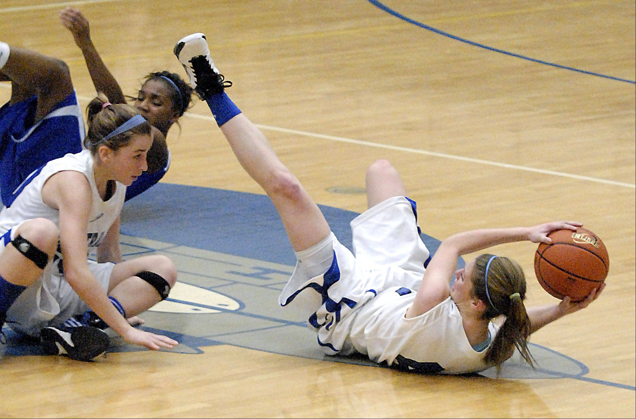 Burlington Central's Kayla Ross hangs onto the ball and looks to pass after taking a tumble with teammate Kathleen Ratzek and Larkin's Lindsey Taylor in the second quarter on Friday, November 16.