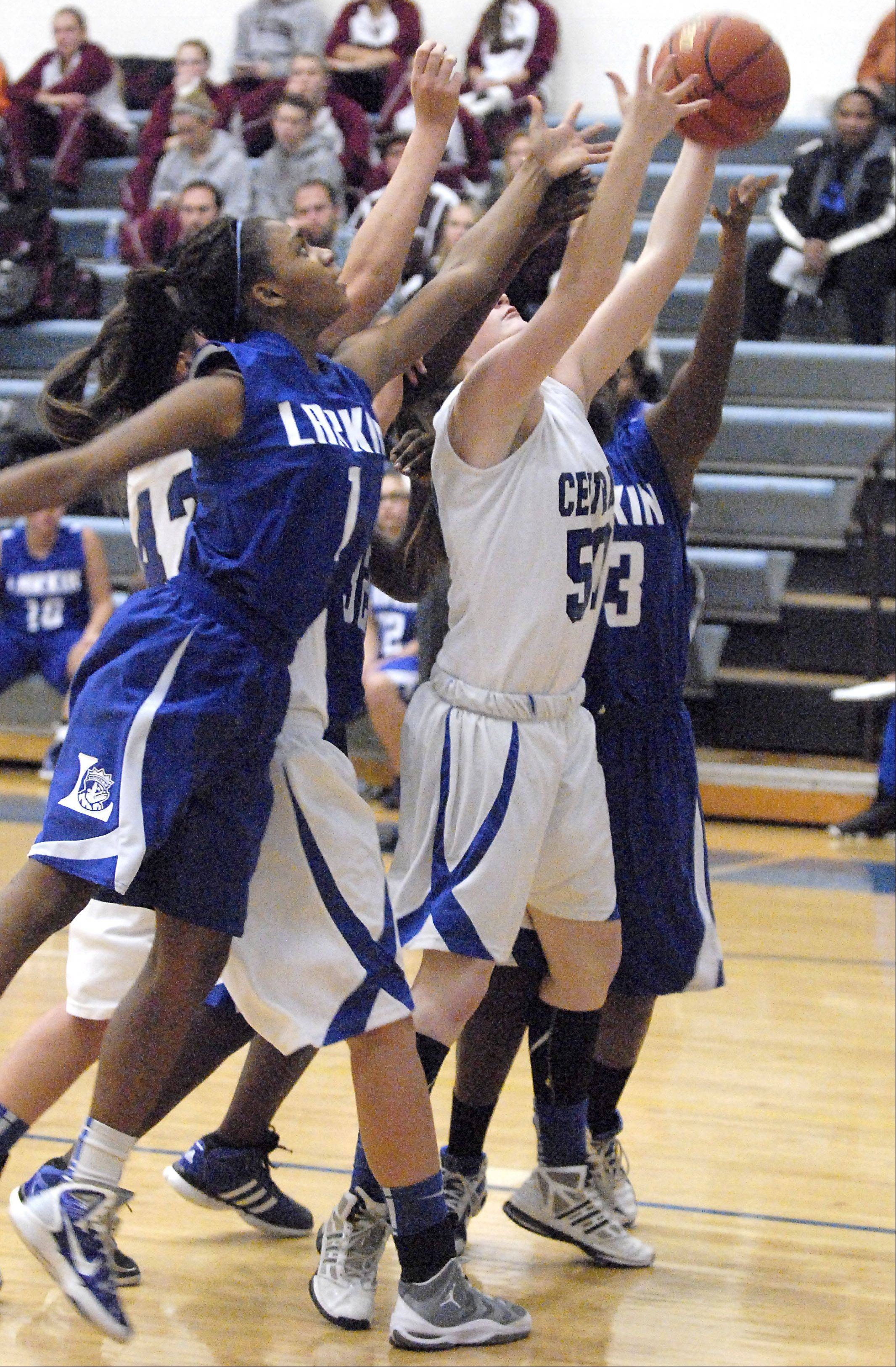 Larkin's Lindsey Taylor and Burlington Central's Rebecca Gerke leap in the pack for a rebound in the first quarter on Friday, November 16.
