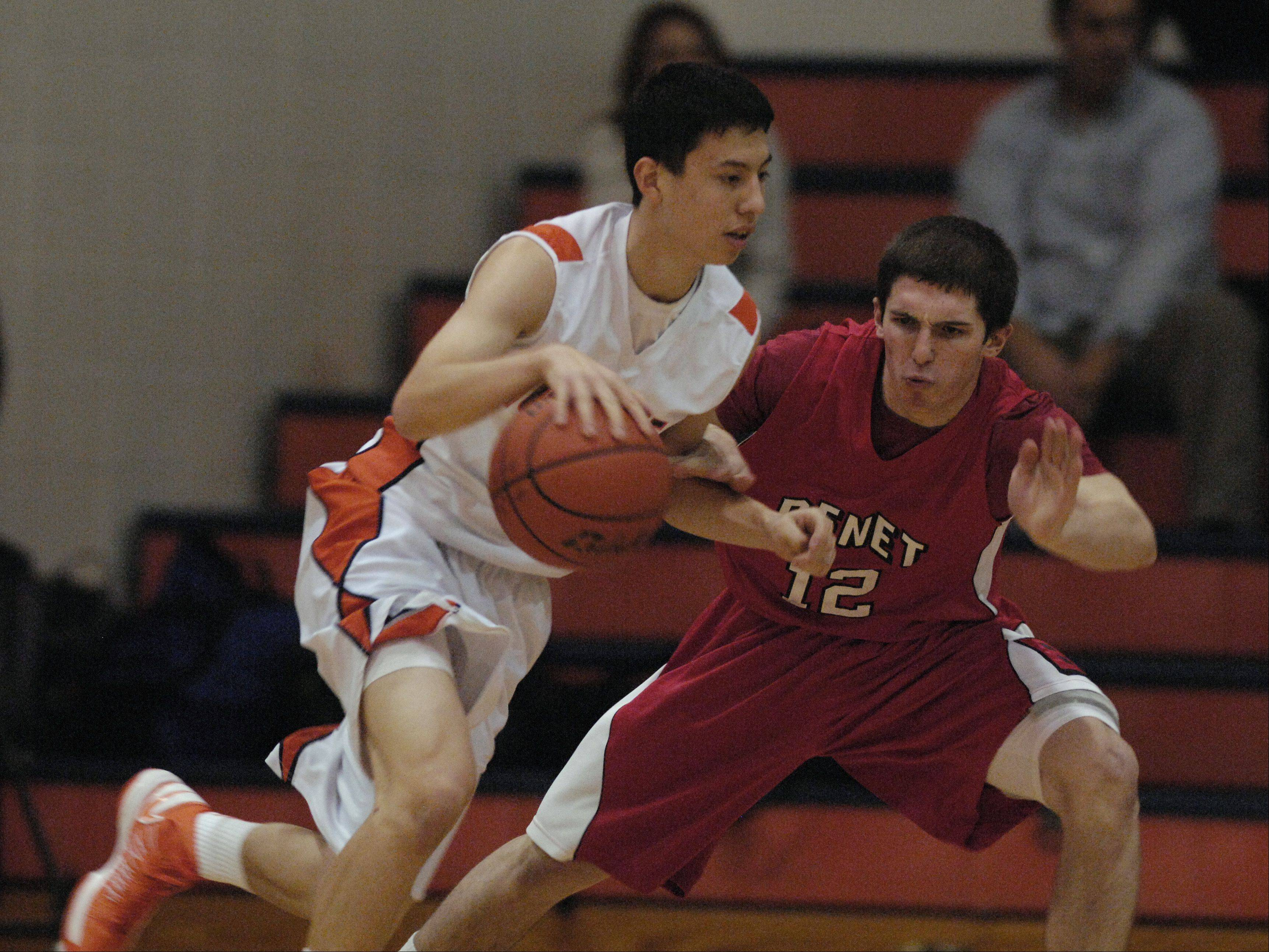 "Jayson Winick of Naperville North drives around Collin Pellettieri of Benet Academy during the ""Hoops for Healing"" boys basketball tournament, Monday in Naperville."
