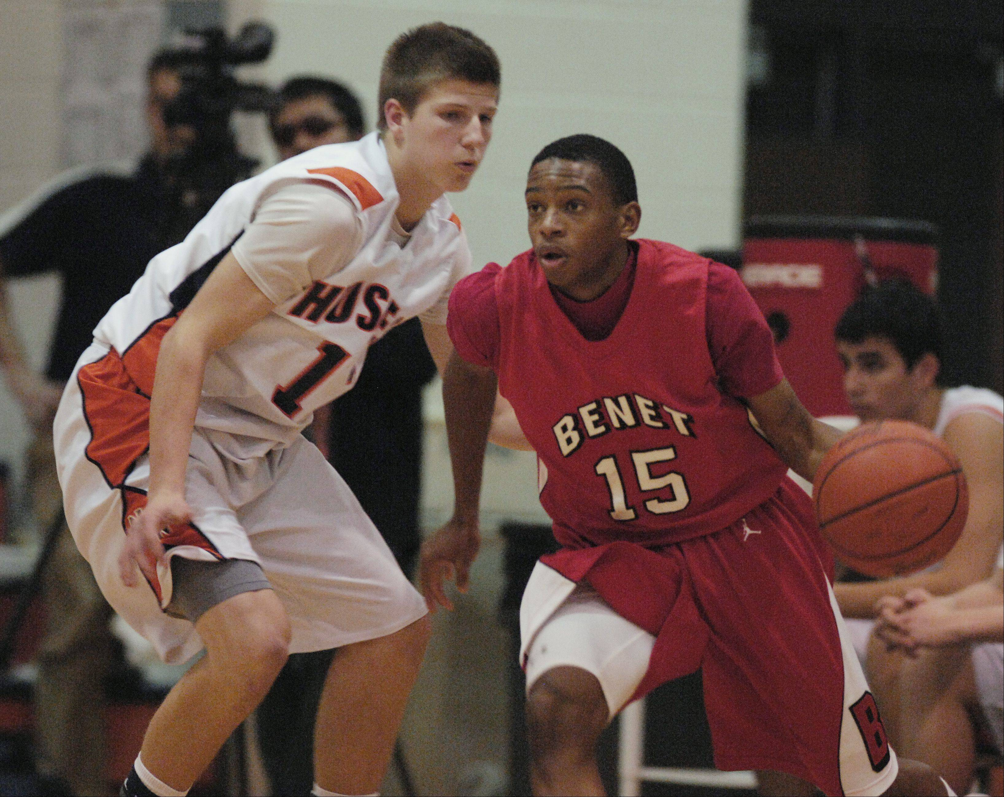 "Josh Yesufu (15) of Benet Academy drives around Zack Tuxhorn of Naperville North during the ""Hoops for Healing"" boys basketball tournament, Monday in Naperville."