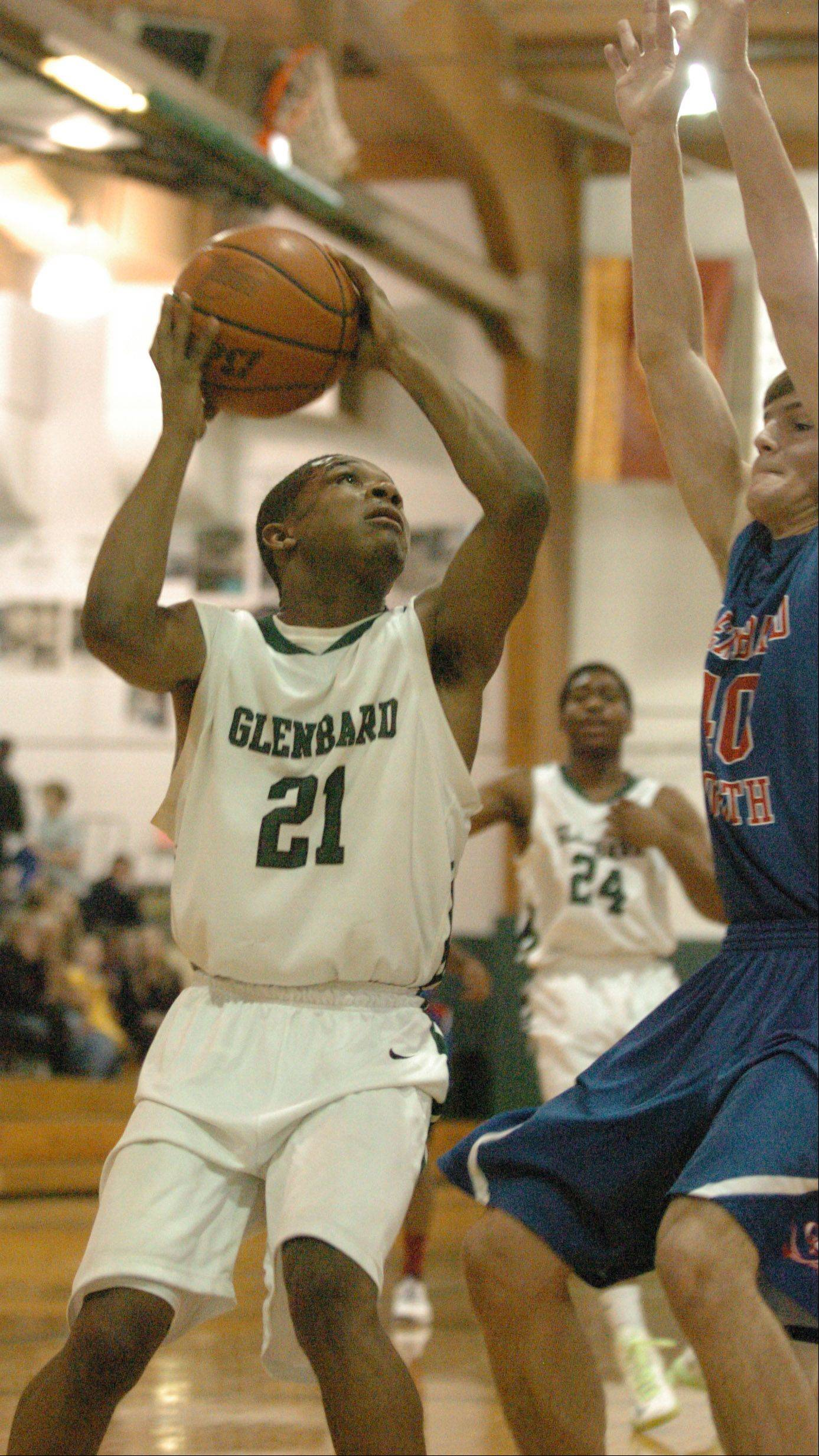 Dikiria Washington puts up a shot around John Marks of Glenbard South during the Glenbard south at Glenbard West boys basketball District 87 Tournament Tuesday.