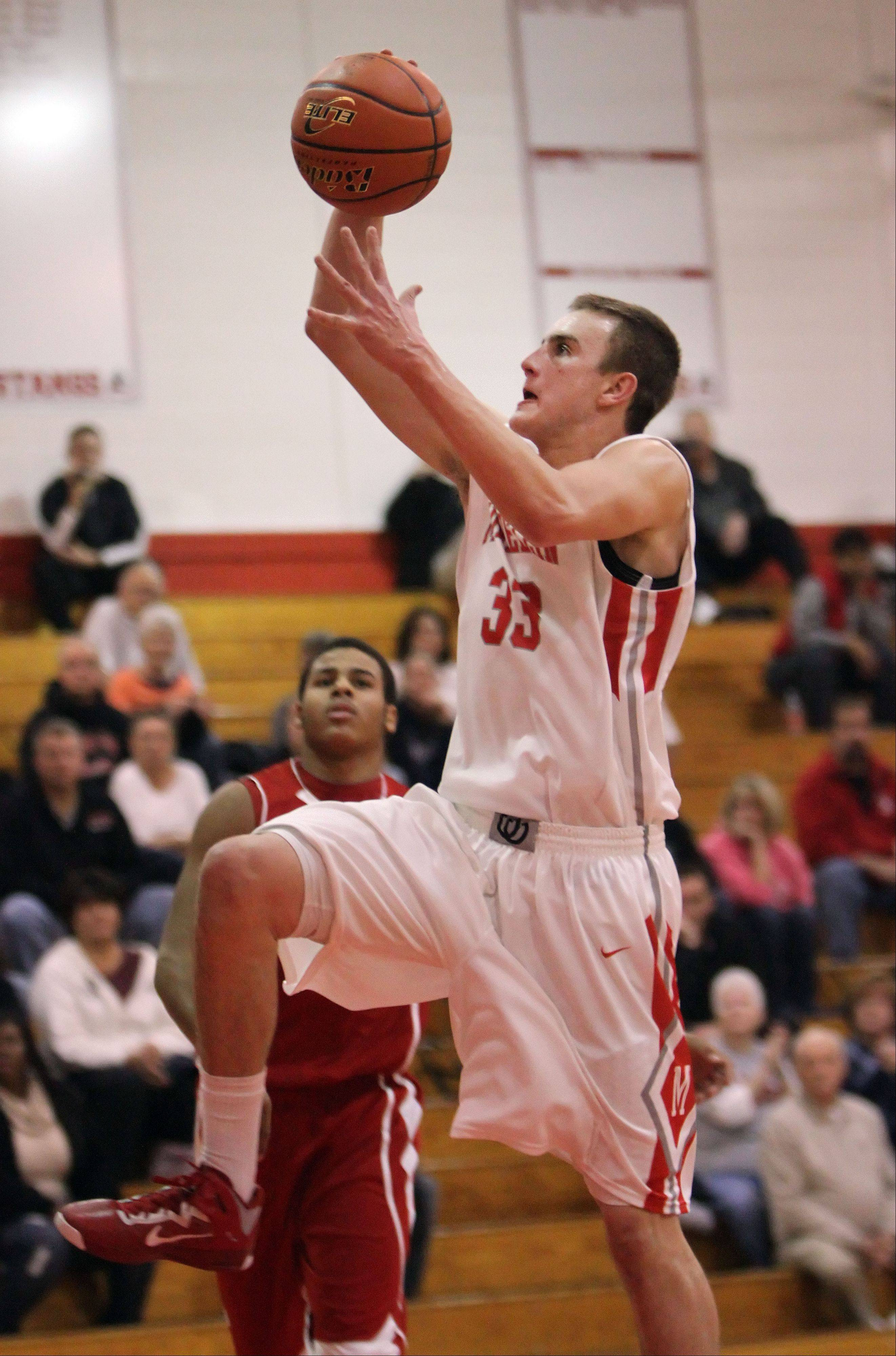 Mundelein's Sean O'Brien drives in for a dunk during their game against Lakes Tuesday night at Mundelein.