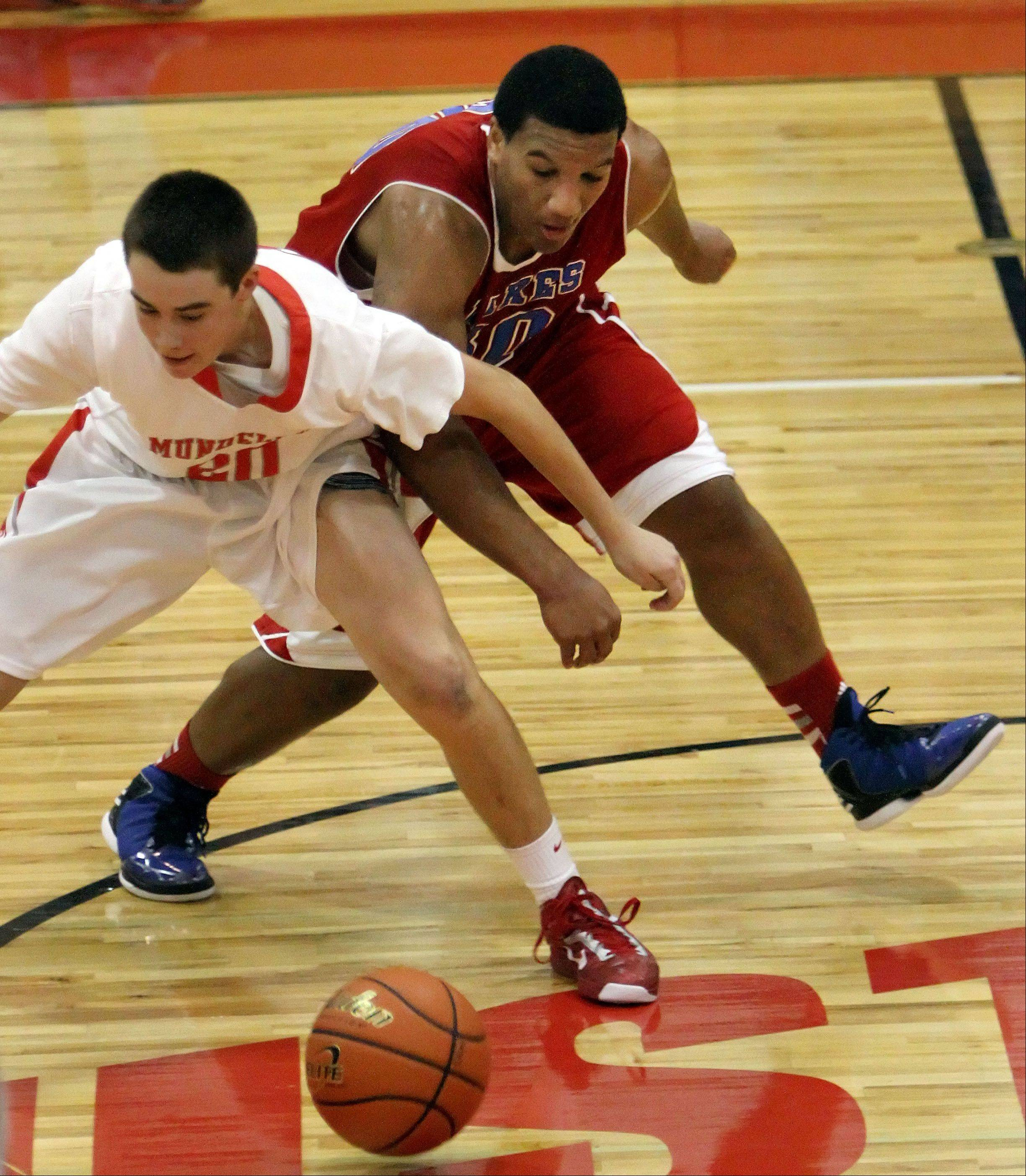 Mundelein's Derek Parola and Lakes' Direll Clark battle for a loose ball Tuesday night at Mundelein.