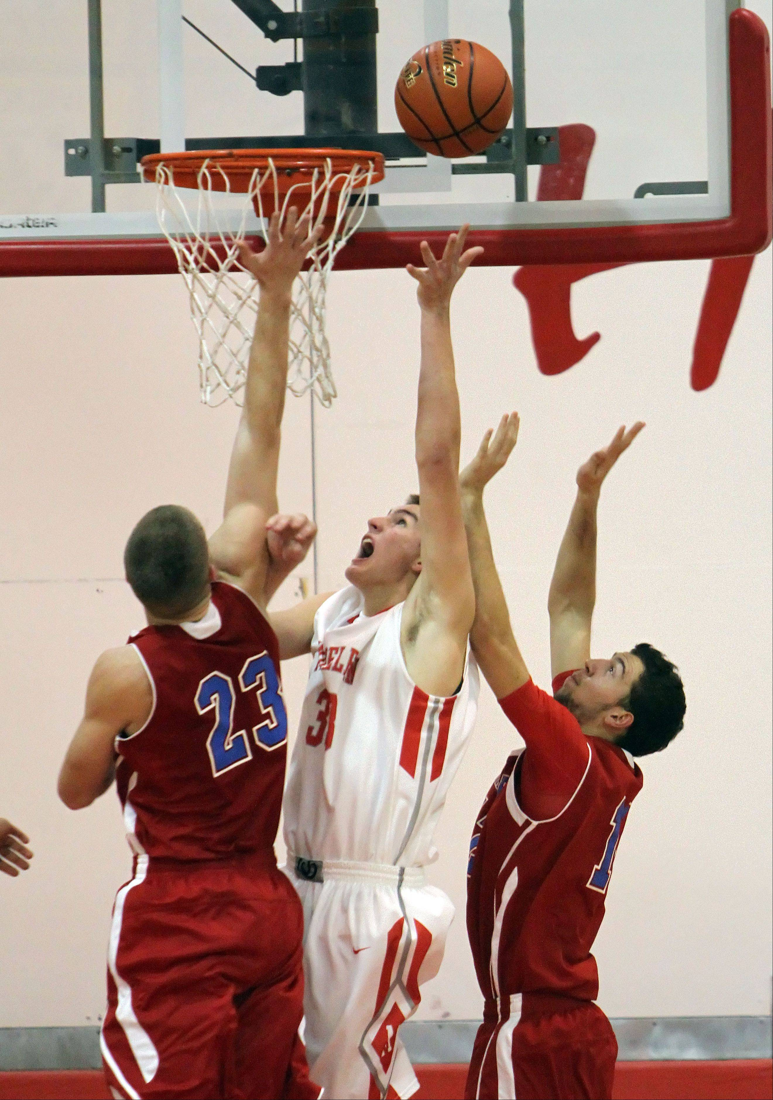 Mundelein's Sean O'Brien splits in Lakes' Jake Kohler, left, and Michal Tomasiewicz on Tuesday night at Mundelein.