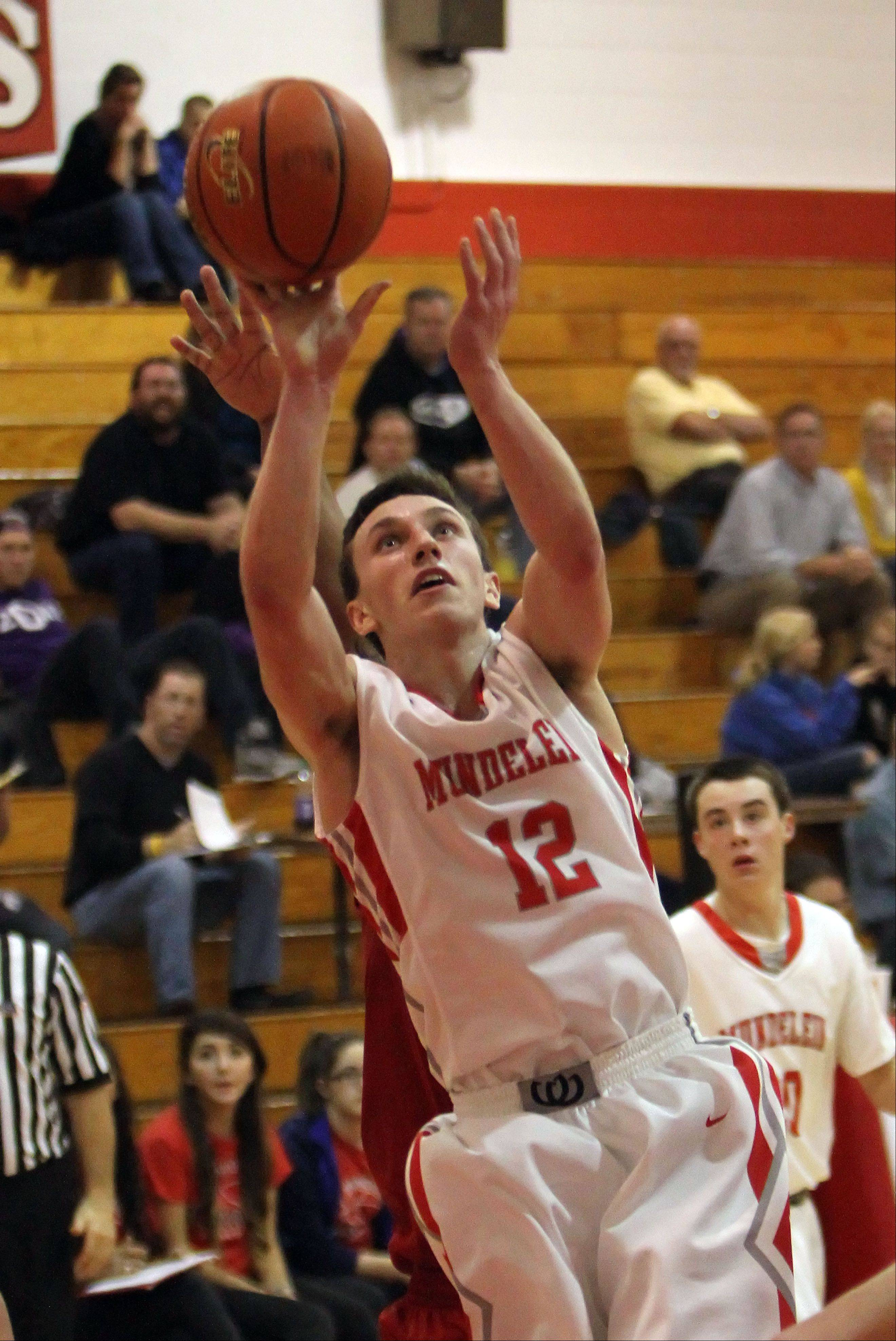 Mundelein's Quinn Pokora drives to the hoop against Lakes on Tuesday night at Mundelein.