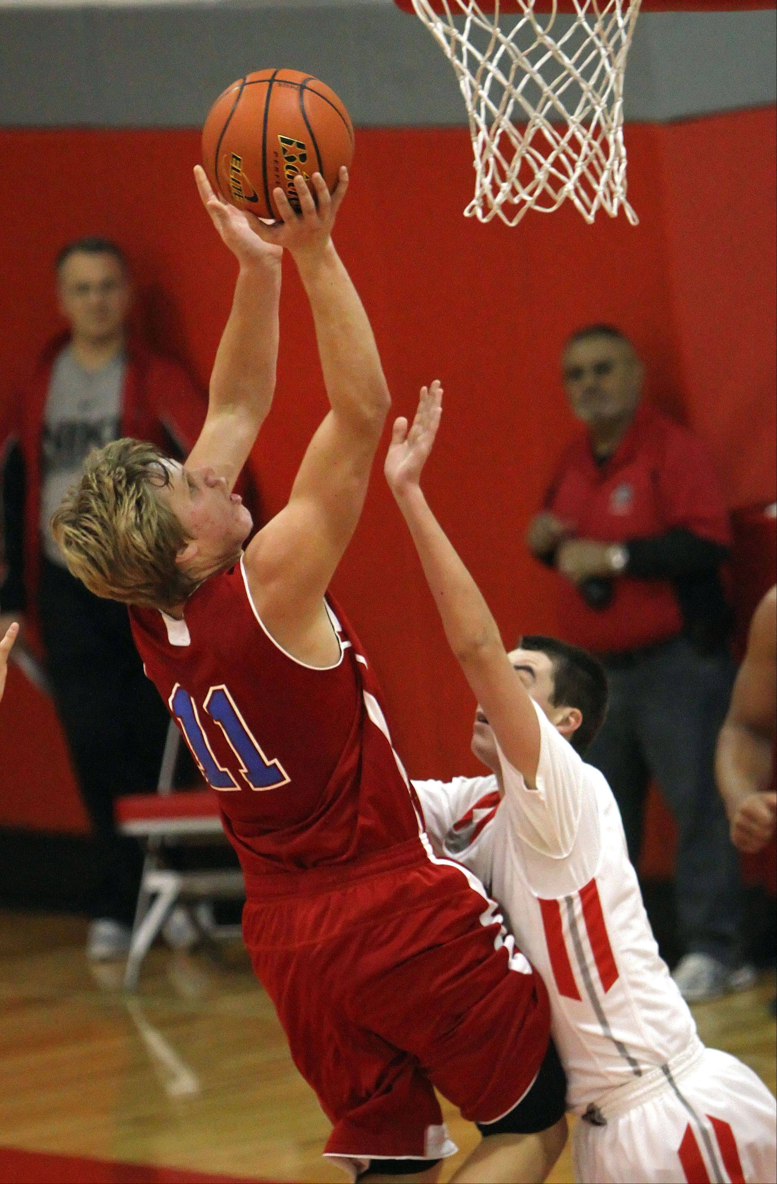 Lakes' Justin Burgeron, left, drives on Mundelein's Derek Parola on Tuesday night at Mundelein.