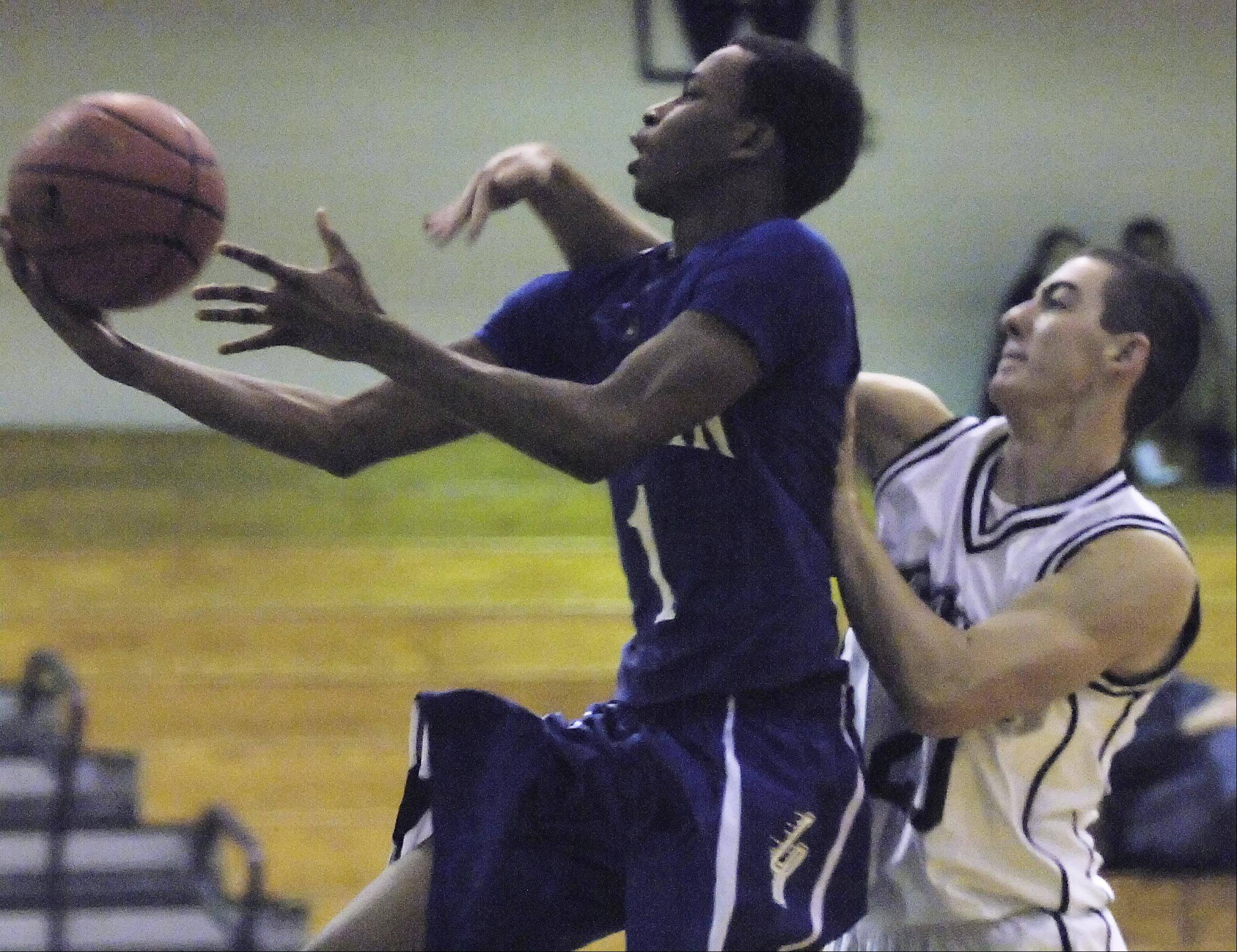 Cary-Grove's Clay Marunde fouls Larkin's Quantice Hunter Tuesday in the Hoops for Healing Tournament in Woodstock.