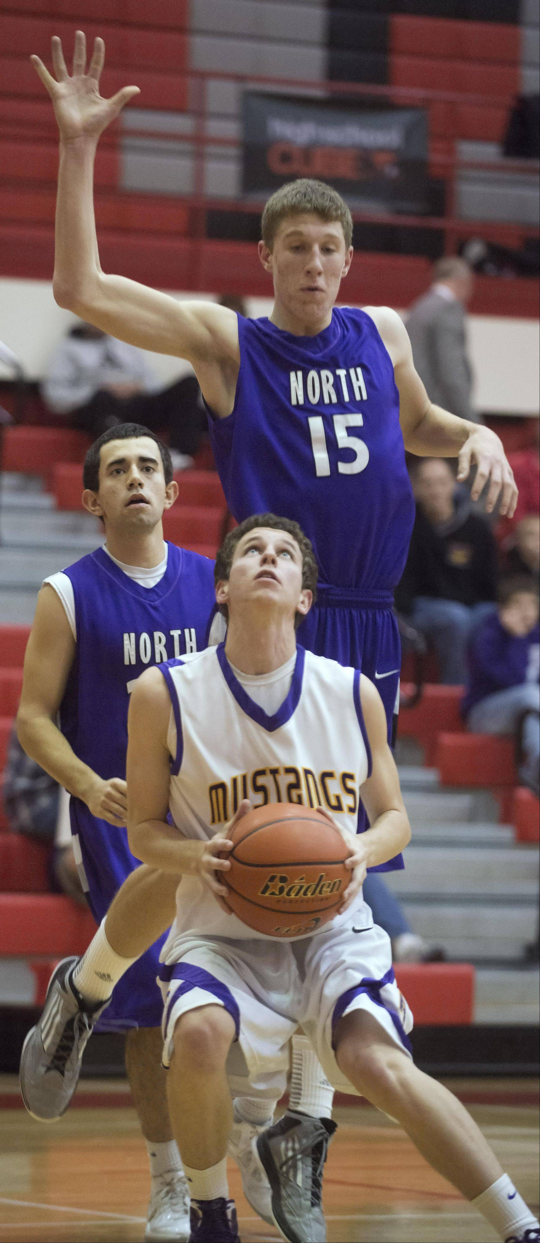 Rolling Meadows' Adam Pavlakis attempts to fake Niles North's Billy Voitik before taking a shot under the basket during Tuesday's game at Palatine.