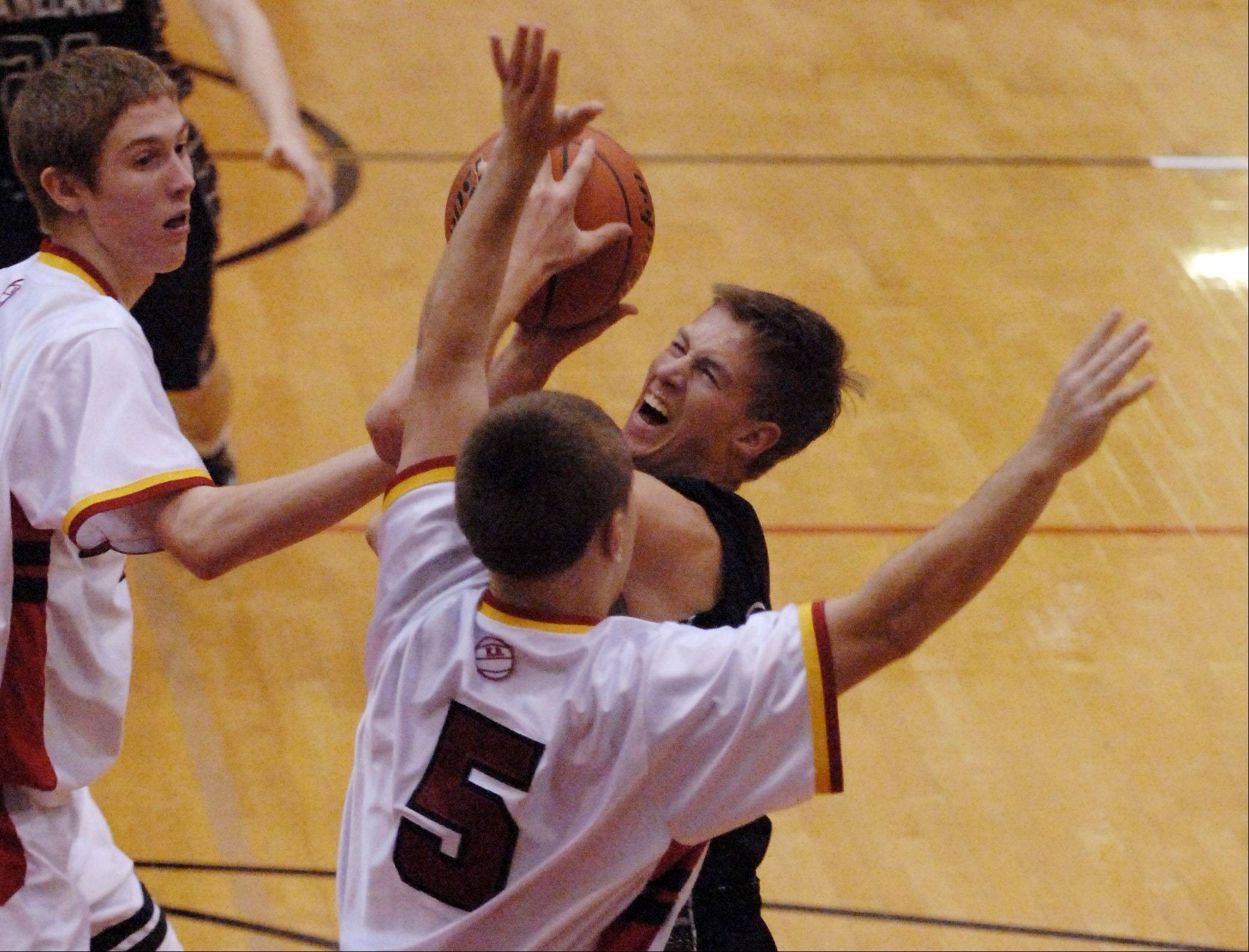 Kaneland's Dan Miller fights through a double team to get up a shot against Batavia during Wednesday's game at Batavia.