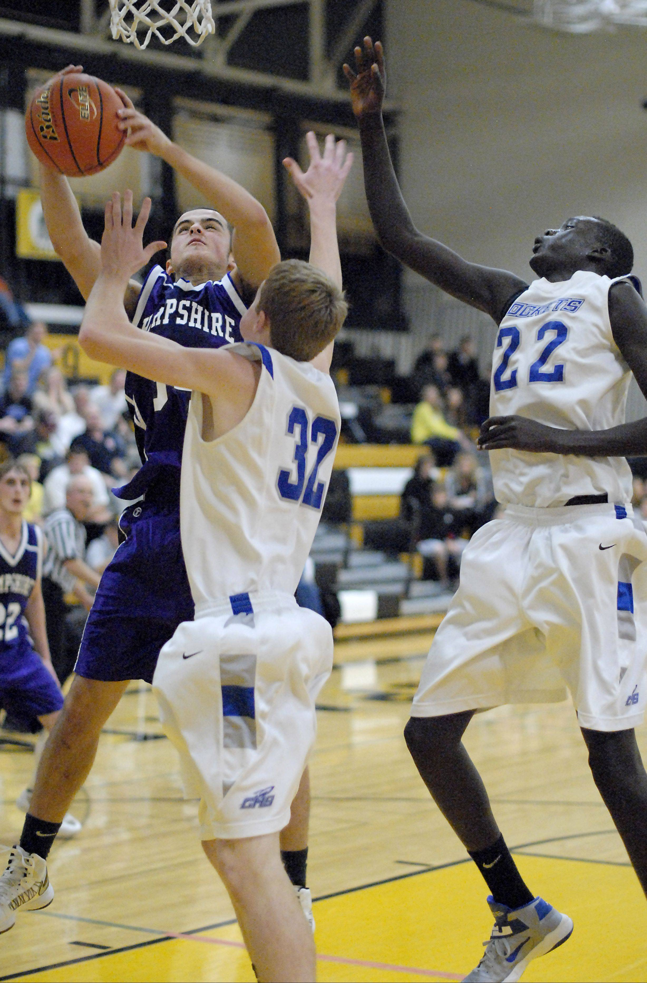 Hampshire's Michael Dumoulin grabs a rebound from Burlington Central's Sean Fitzgerald and Moter Deng in the second quarter of the Sycamore tournament on Wednesday.