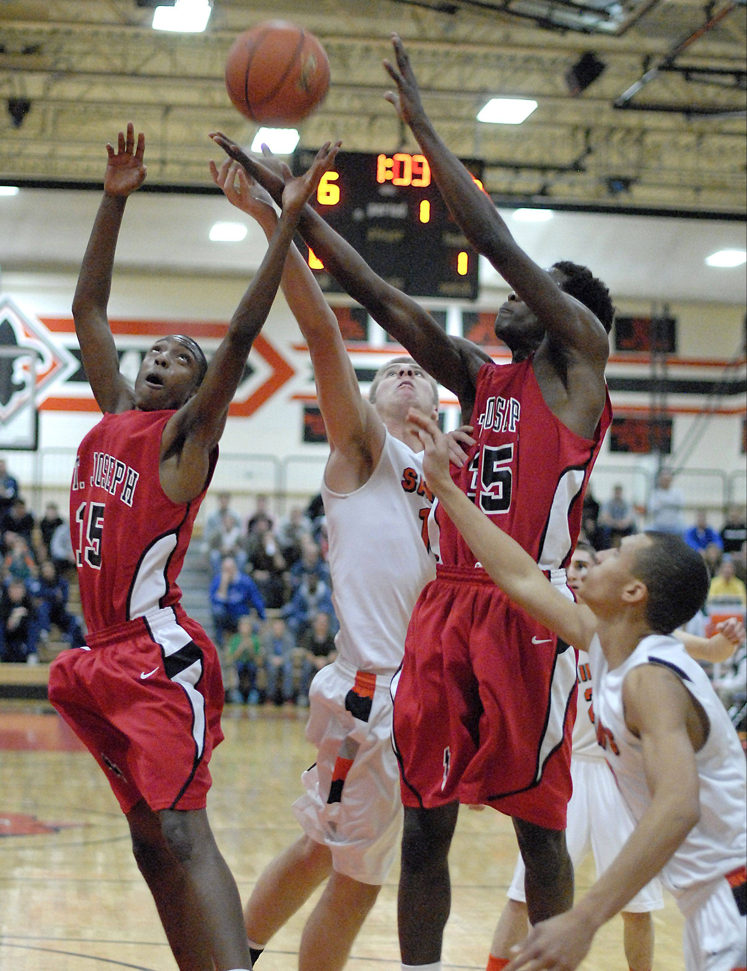 St. Charles East's Ben Skoog is wedged between St. Joseph's Loren Horton and Karriem Simmons as they fight for a rebound in the first quarter on Friday.