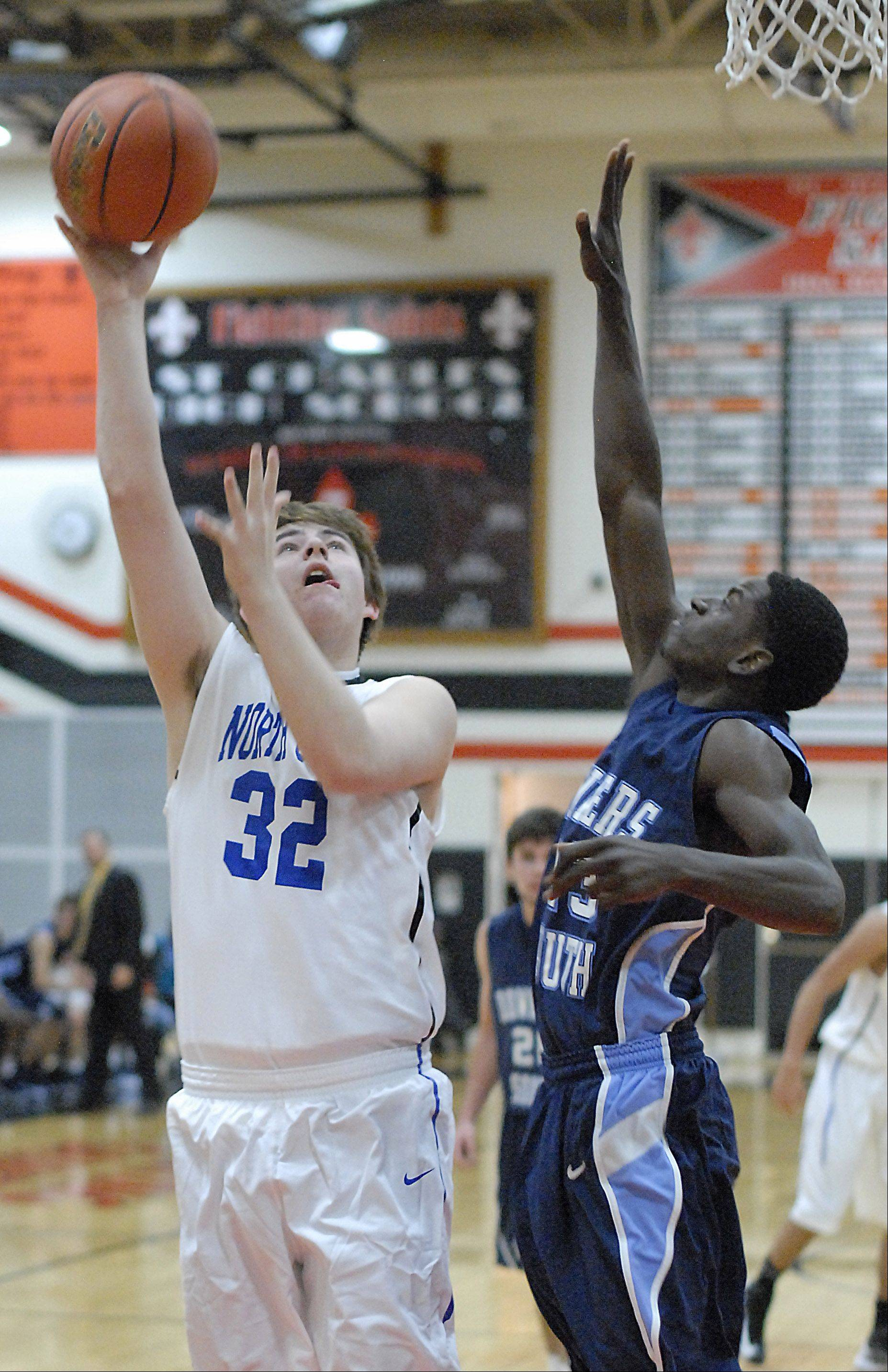 St. Charles North's Jack Callaghan shoots over an attempted block by Downers Grove South's Paul Engo III in the third quarter on Friday, November 23.