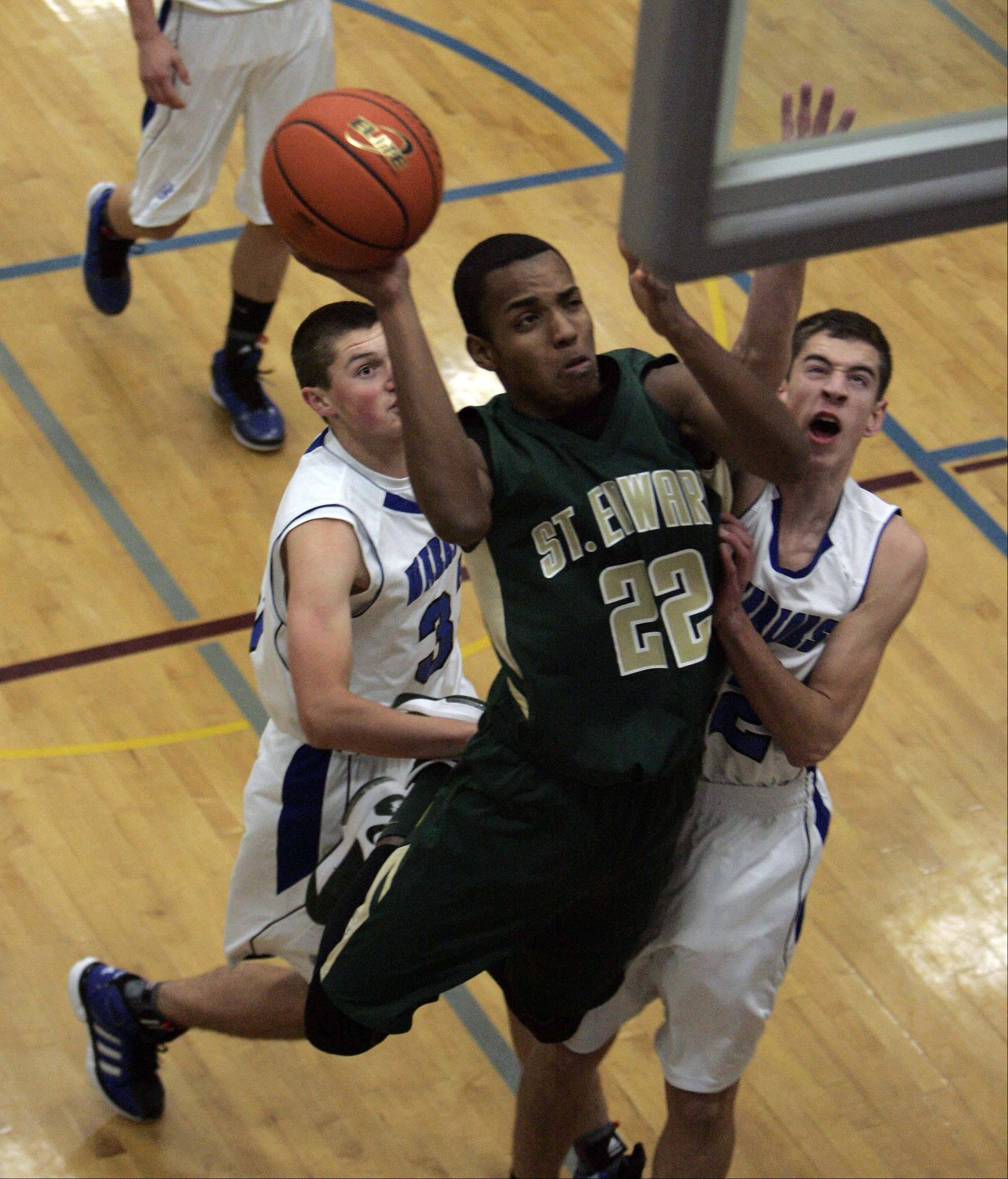 St. Edward forward Adrian Ponce (22) slips through Westminster Christian's Robert Kleczynski (33) and Colin Brandon (42) during the 6th Annual Warrior Thanksgiving Basketball Classic in Elgin Friday.
