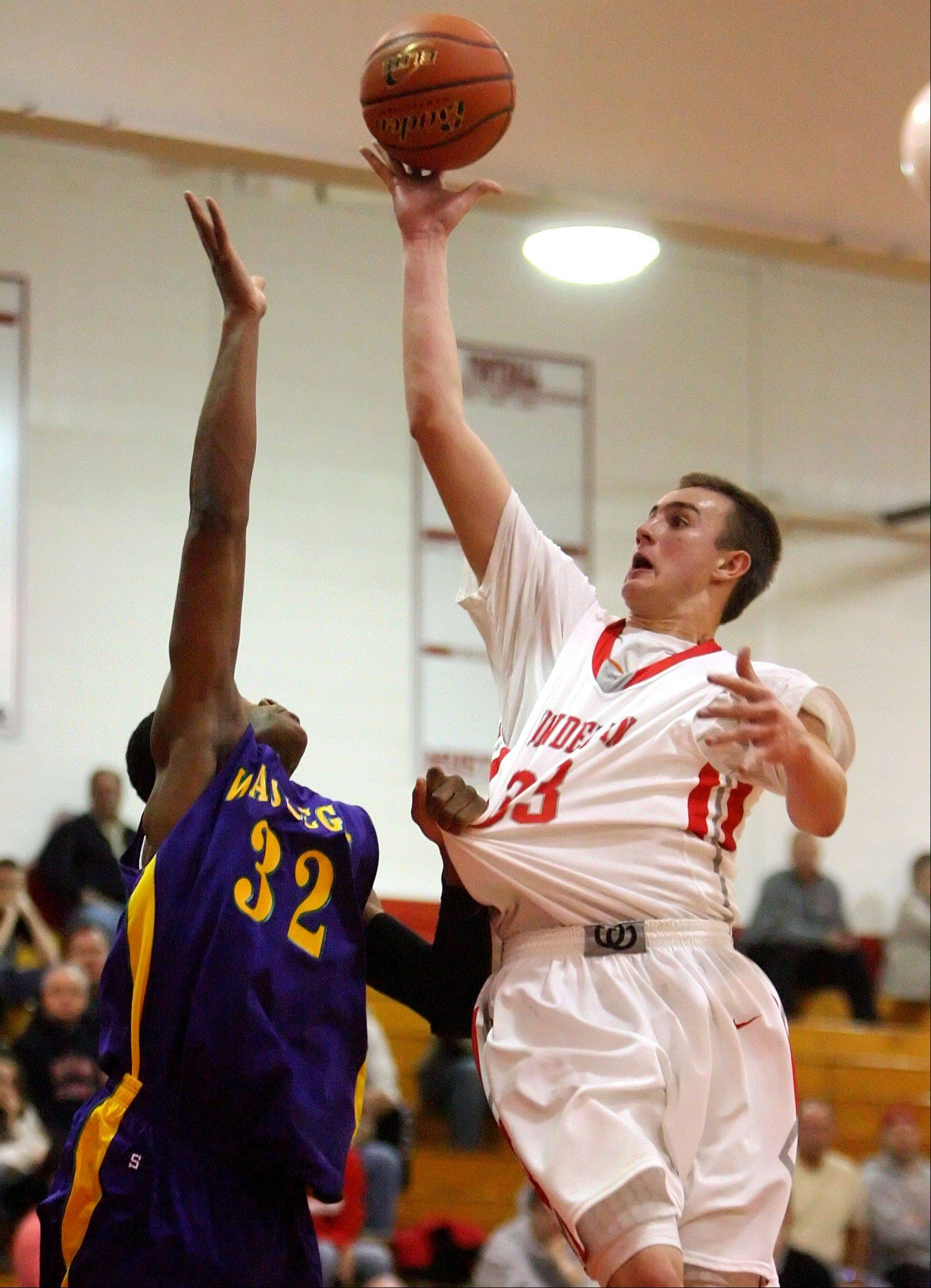 Mundelein's Sean O'Brien, right, drives on Waukegan's Jerome Davis on Friday night at Mundelein.