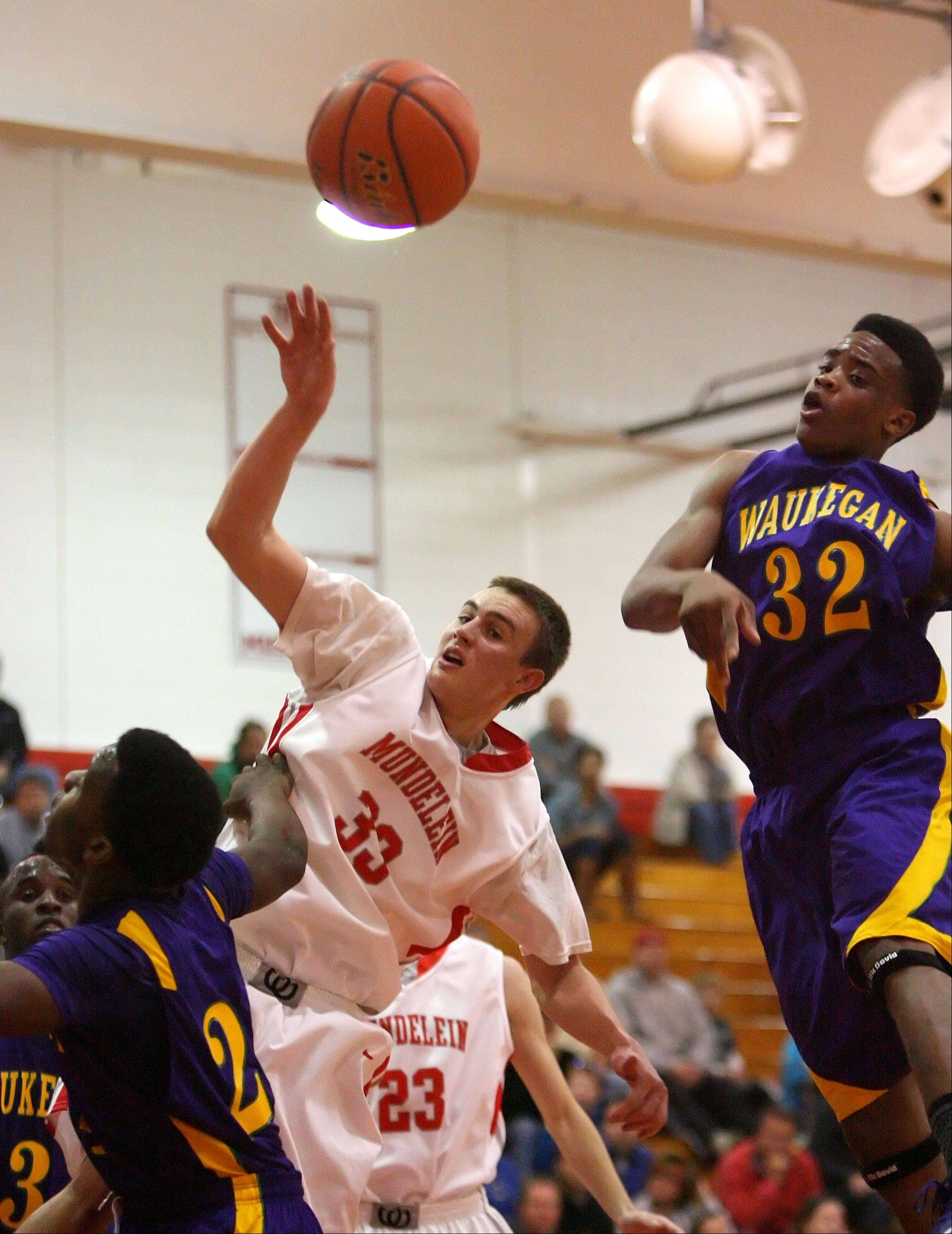 Mundelein's Sean O'Brien, center, drives on Waukegan's Jerome Davis, right, and Quintin Davis on Friday night at Mundelein.