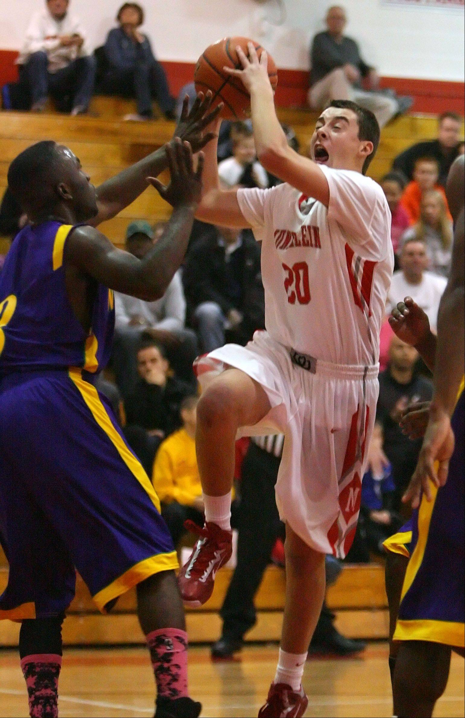 Mundelein's Derek Parola, right, drives on Waukegan's Cornell Fort on Friday night at Mundelein.