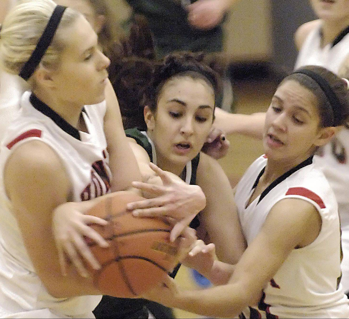 Huntley freshmen Ali Andrews, left, and Kayla Barreto battle with Bartlett's Elizabeth Arco for possession of the basketball. Huntley is off to a 4-1 start to the season.