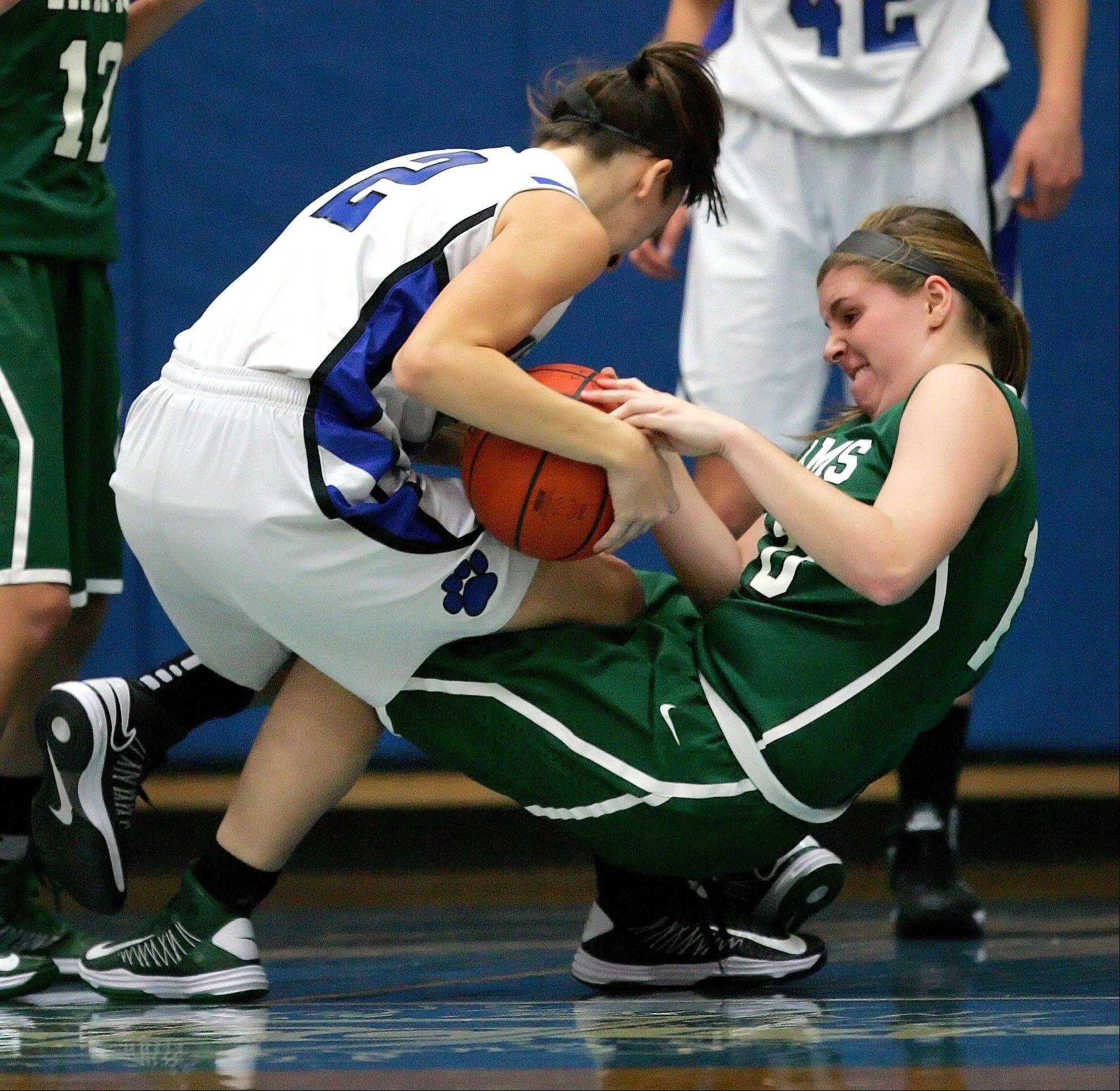Vernon Hills' Alina Lehocky , left, and Grayslake Central's Maddy Miller battle for a loose ball Tuesday night at Vernon Hills High School.