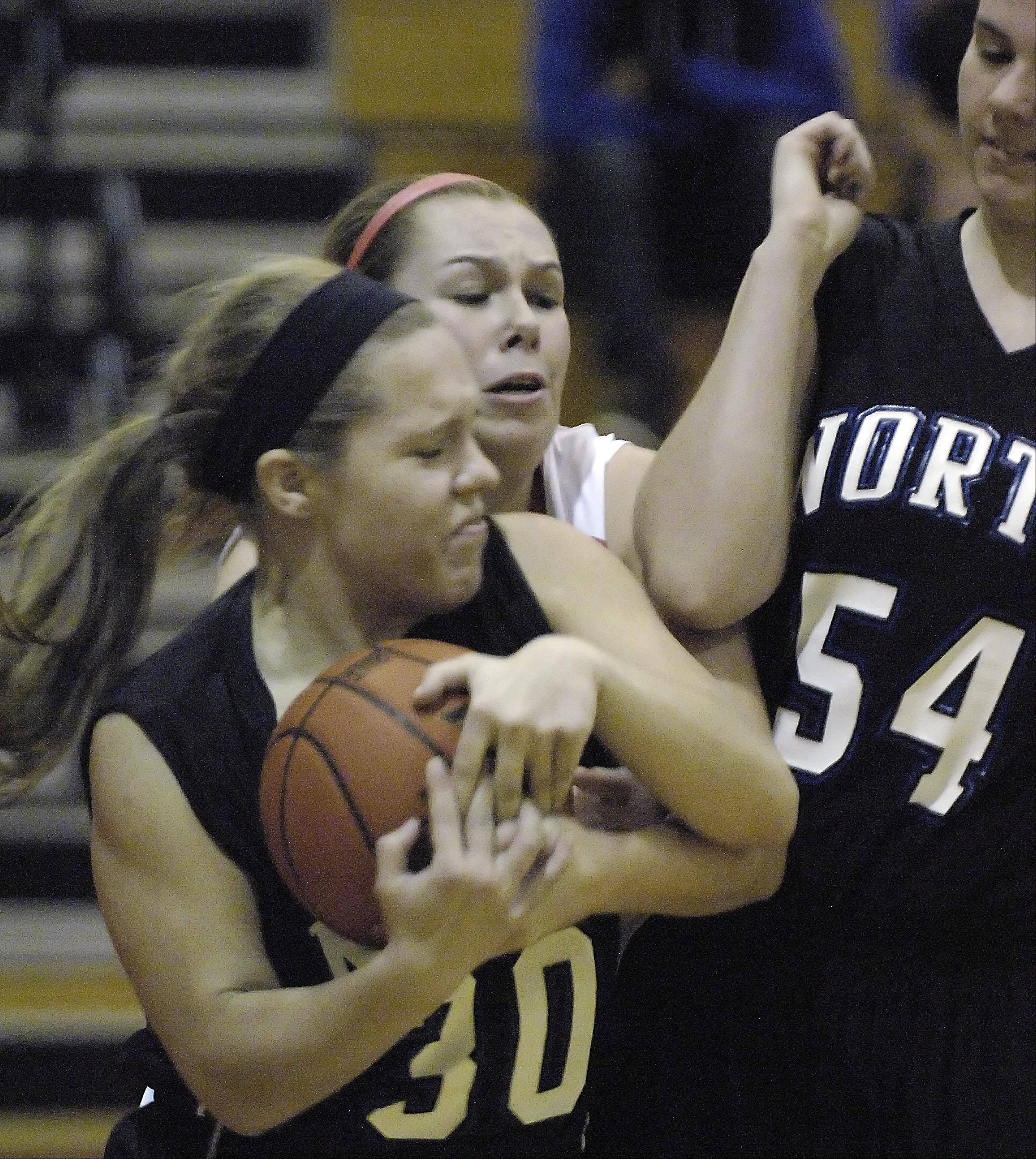 St. Charles North's Ava Tarka and Batavia's Erin Bayram struggle for control of the ball.