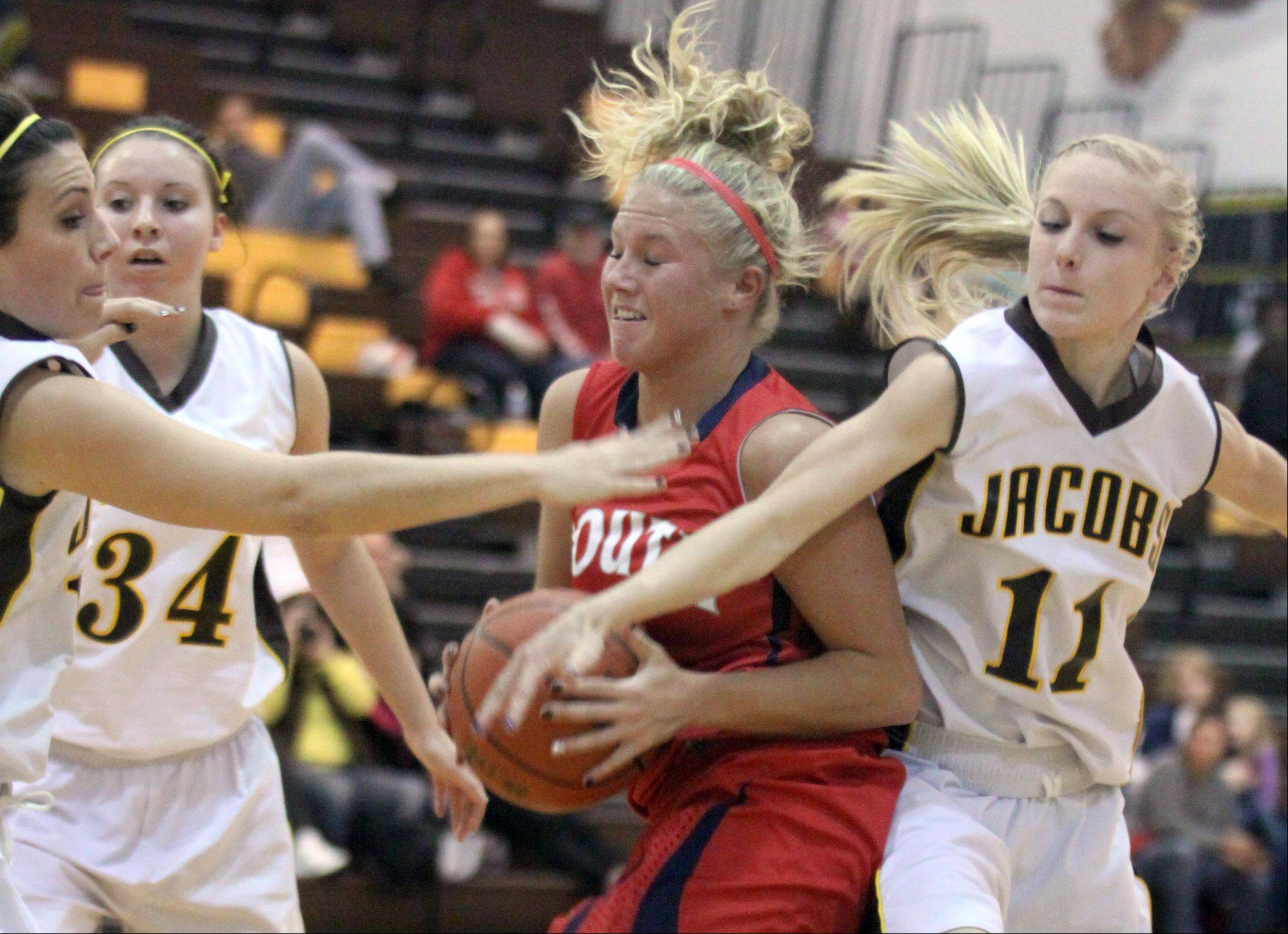 Jacobs' Payton Berg, left, and Lauren Van Vlierbergen, right try to stop the progress of South Elgin's Kara Rodriguez, center, during a varsity basketball game at Algonquin on Tuesday night.