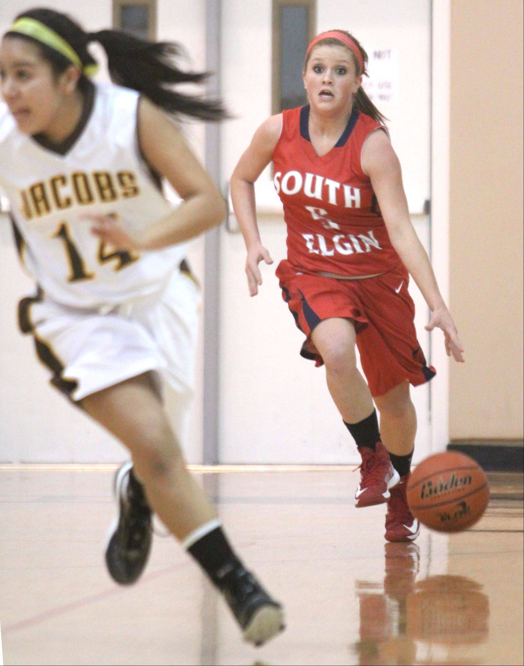Jacobs' Nicky Chapa, left, motors up court as South Elgin's Anna Tracy, right, looks for an open teammate on a fast break during a varsity basketball game at Algonquin on Tuesday night.