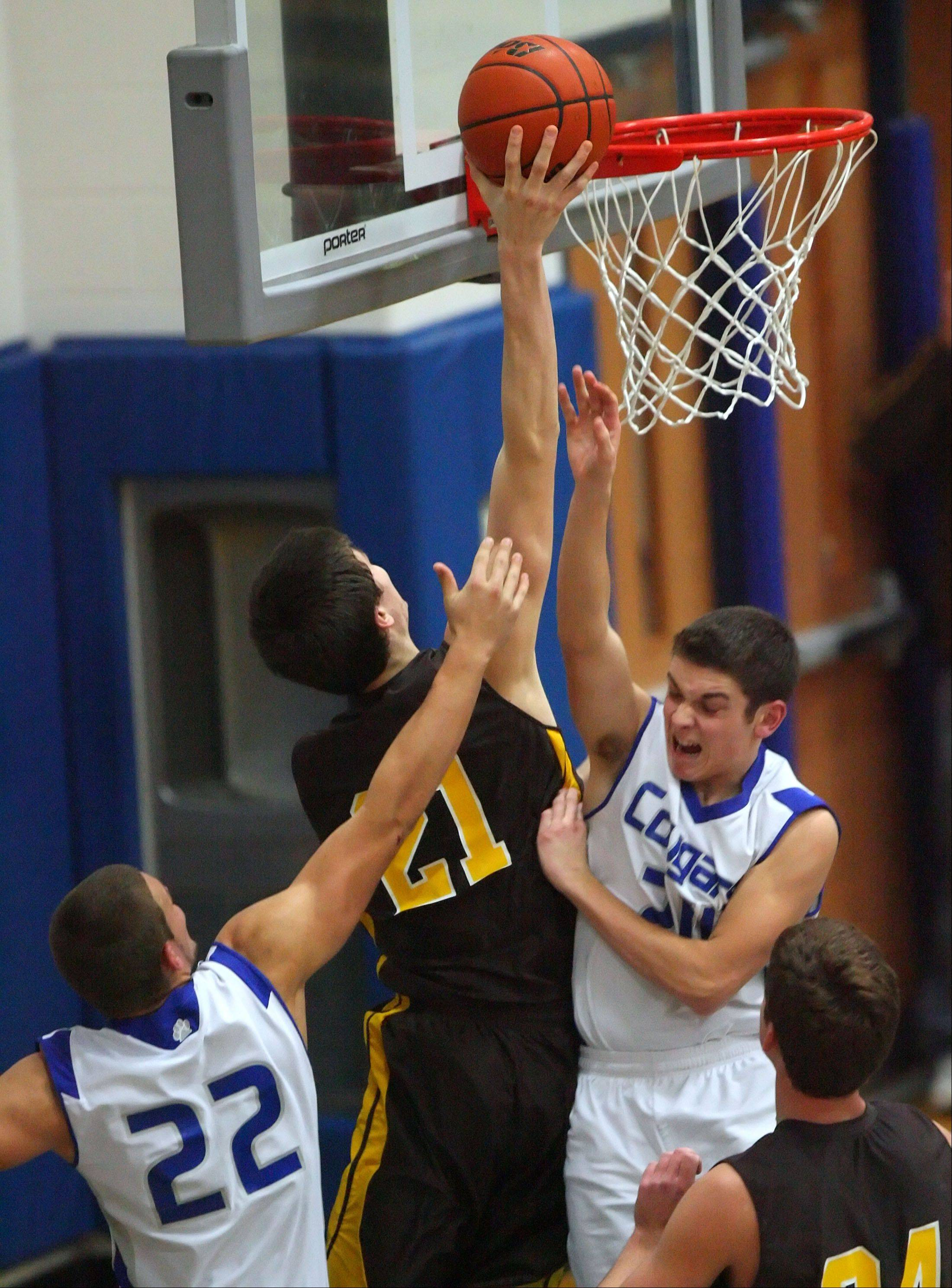 Carmel's Jack George, center, drives to the hoop past Vernon Hills' TJ Flis, left and Michael Mariella .