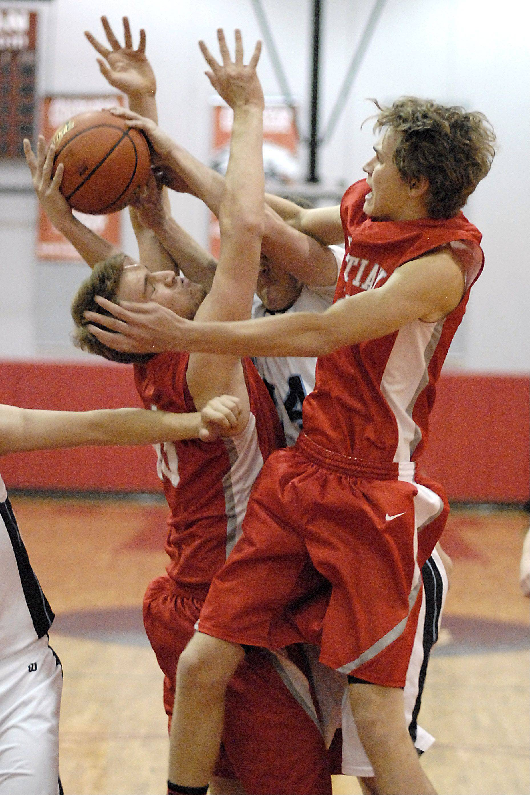 Aurora Christian's Paxton Singer and Zach Singer swarm Joliet Catholic's Ryan Peter for a rebound .