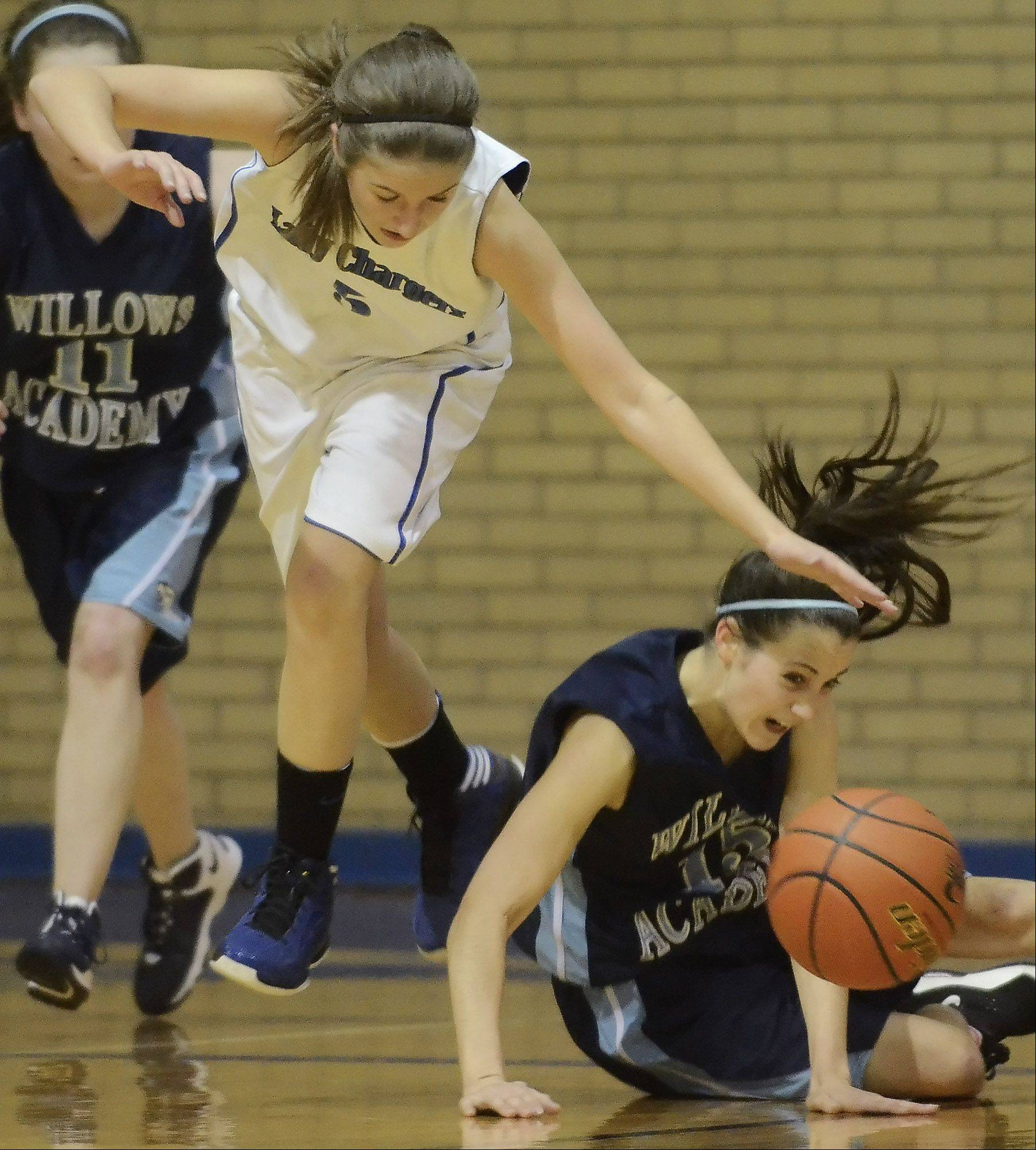 Christian Liberty Academy's Jess Moriarty, left, tries to take control of a loose ball as Keelin McNally of Willows Academy falls to the floor during Wednesday's game.