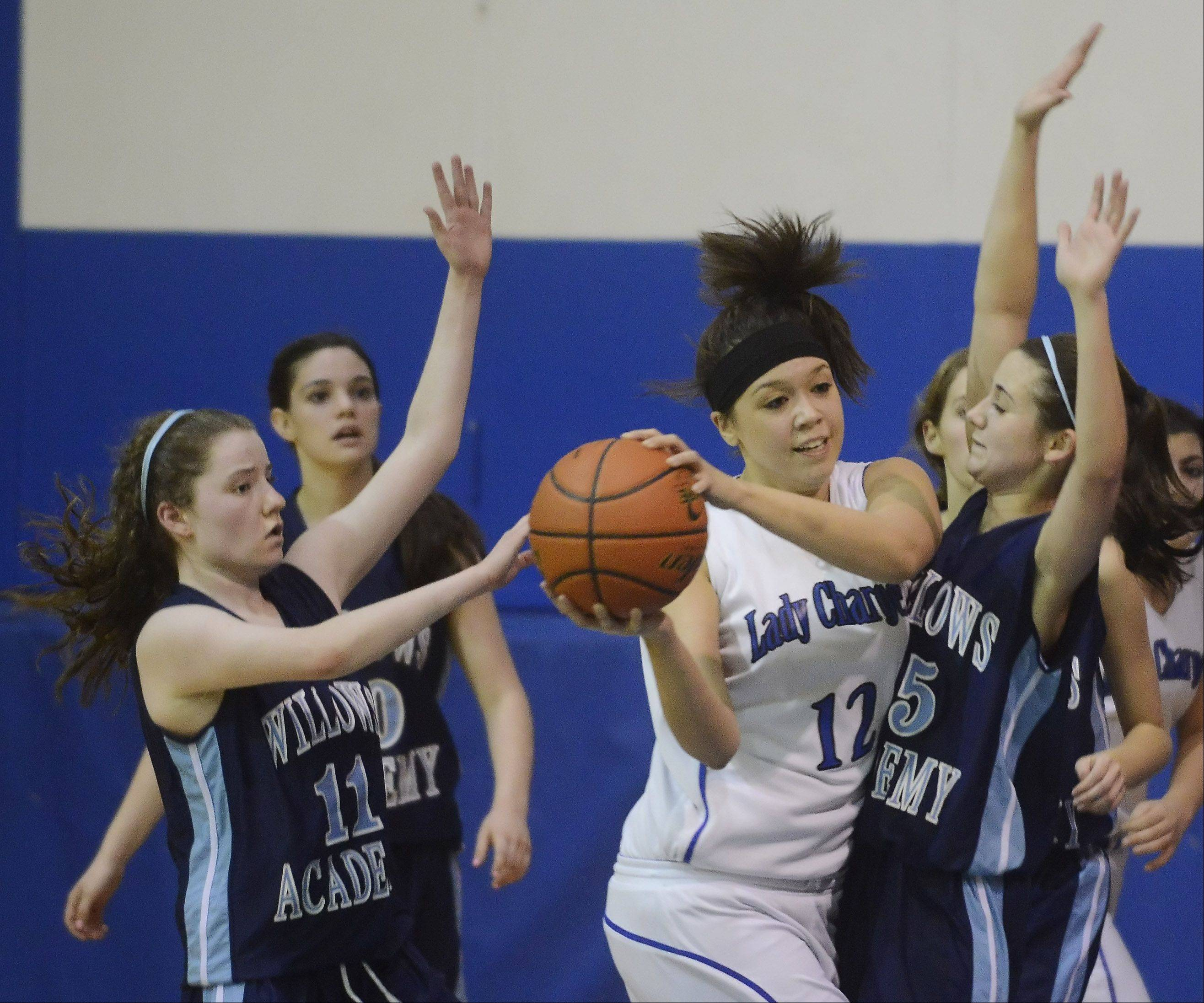 Shelby Hernandez of Christian Liberty Academy, middle, looks for an open teammate as Brigid Walsh, left, and Keelin McNally of Willows Academy defend during Wednesday's game.