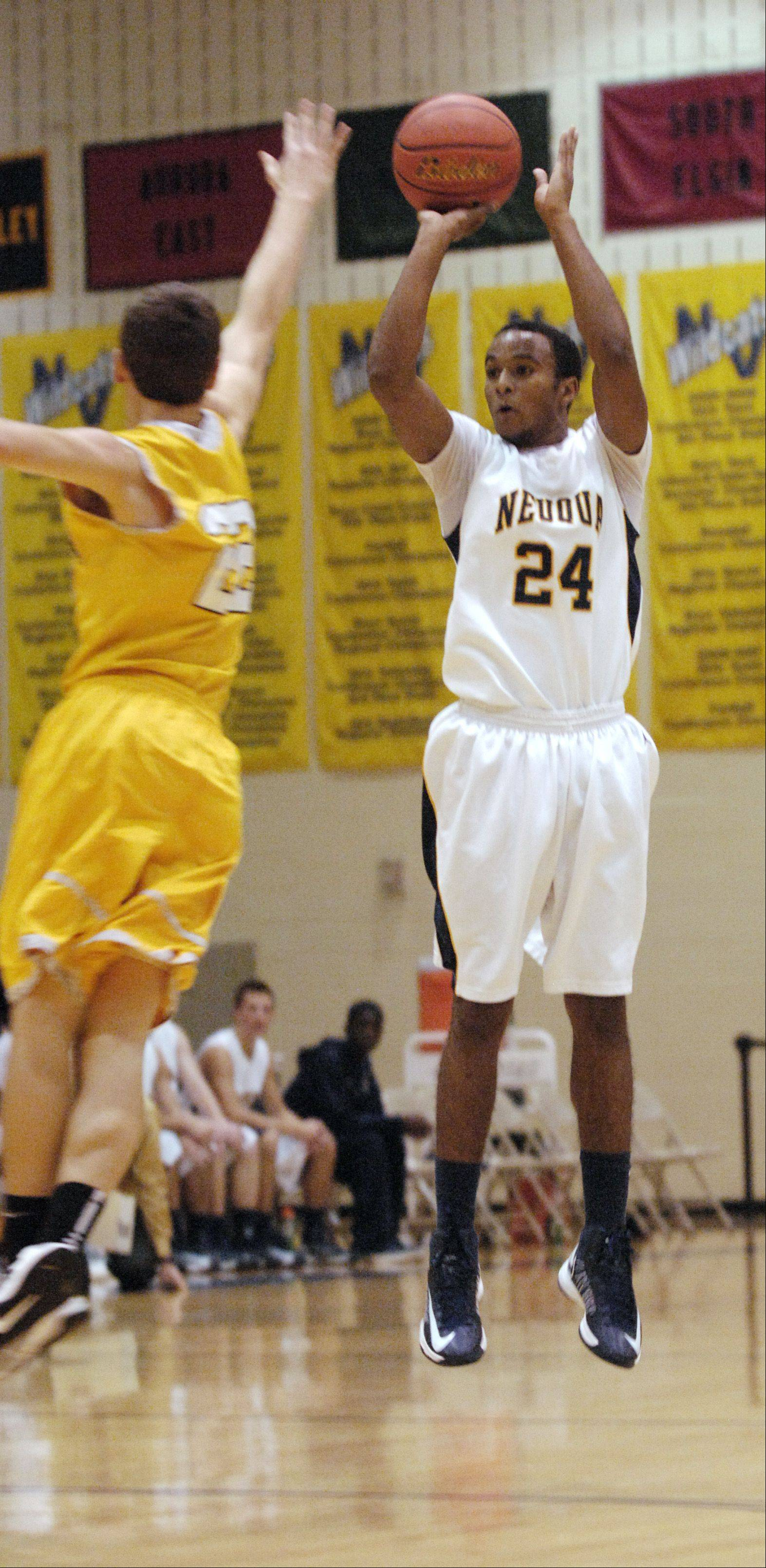 Jabari Sandifer of Neuqua Valley takes a shot over Derek Coleman of Metea Valley.