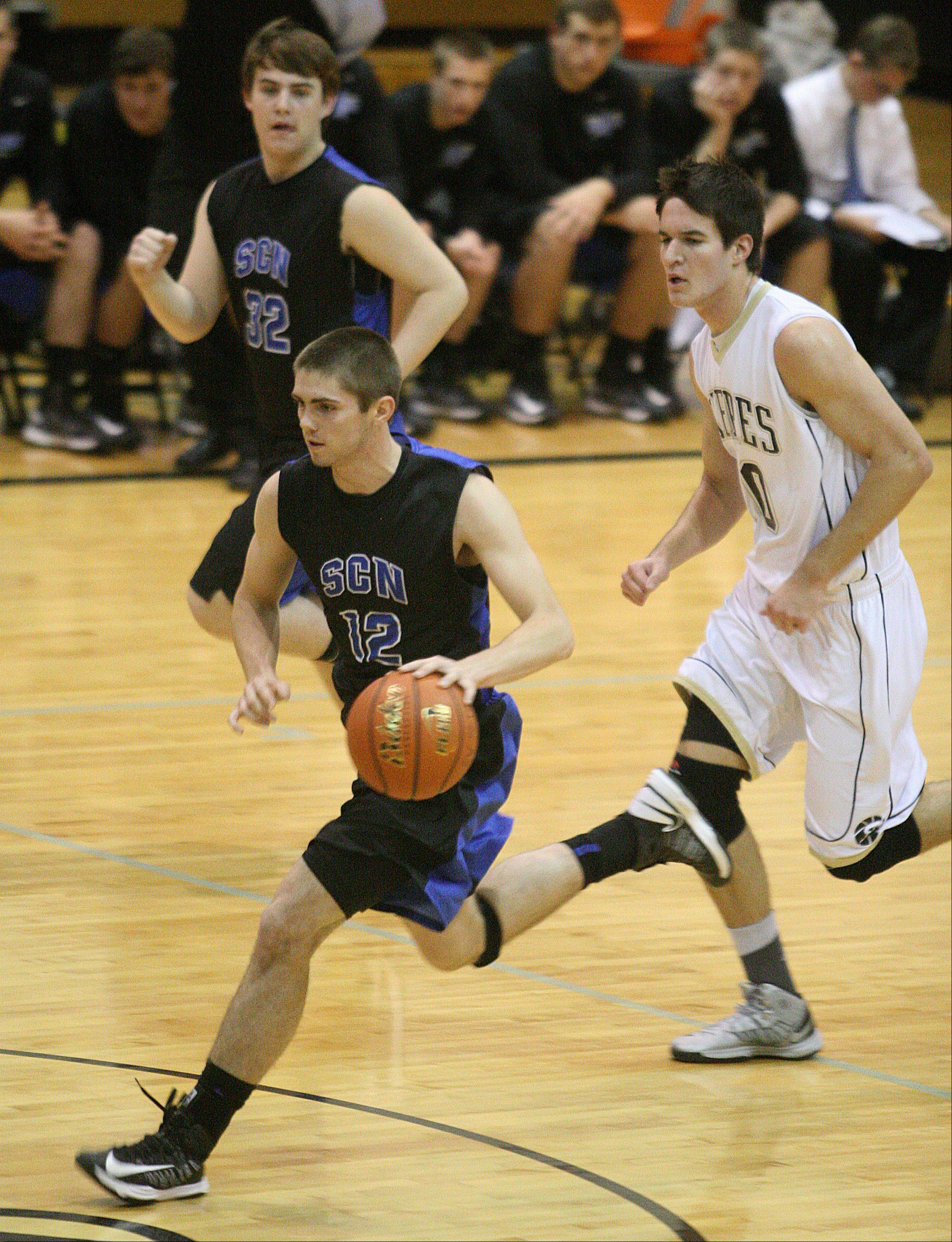 St Charles North's Quinten Payne brings the ball up court.