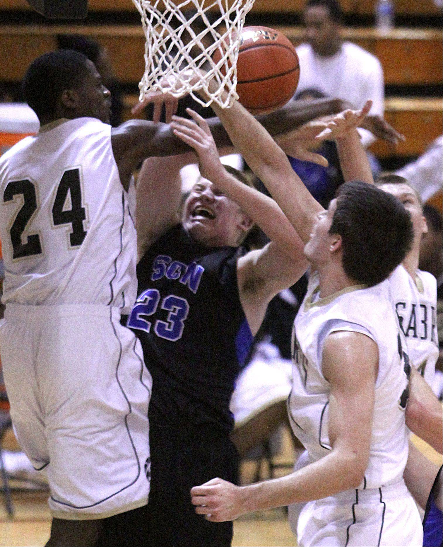 Streamwood's Joel Lightbourne, left, and Zack Harris, right, try to stop St Charles North's Justin Stanko, center.