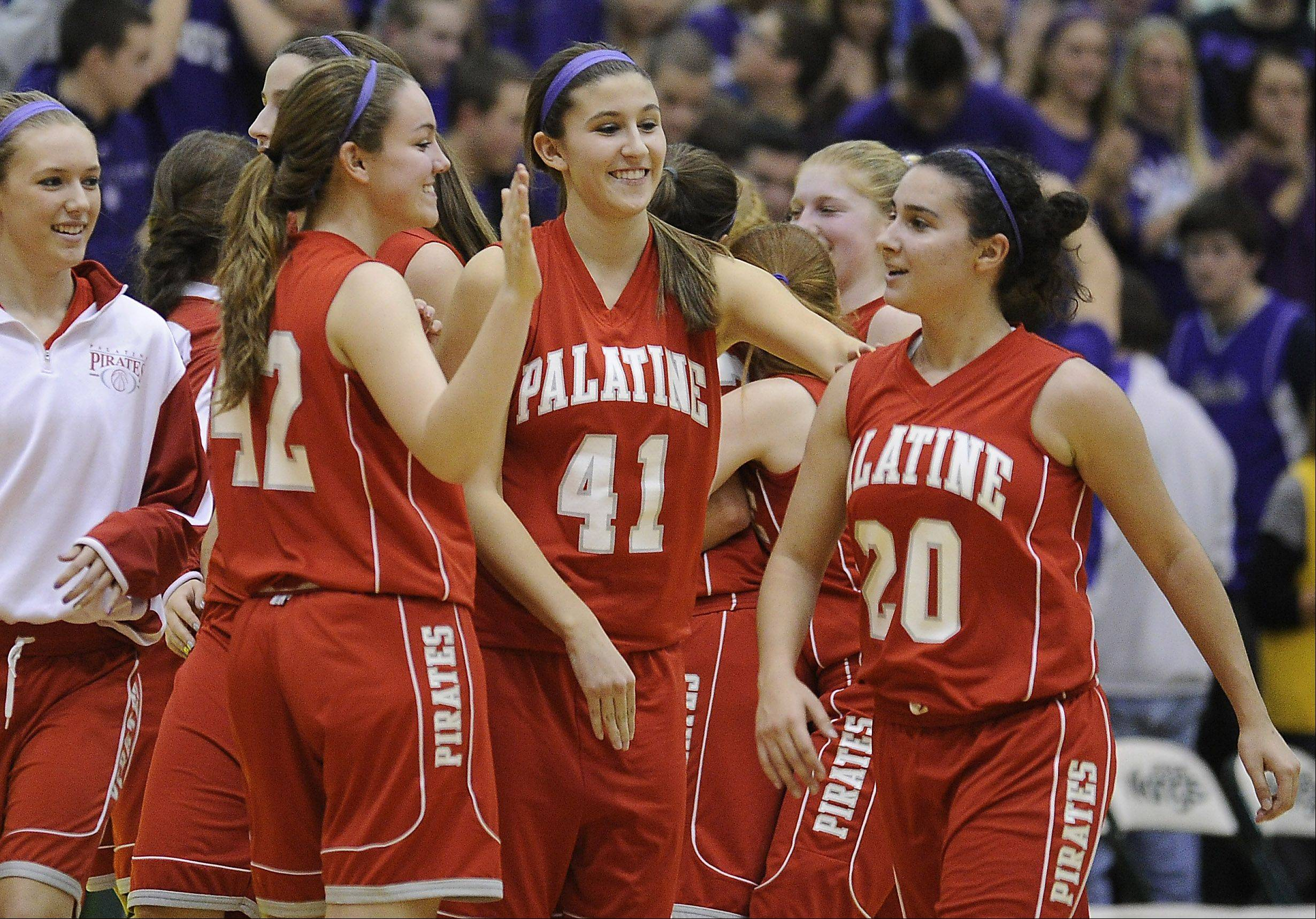 Palatine's Carrissa Multon, Marissa Masini and Nia Pappas celebrate their victory over Fremd in the girls varsity basketball game at Fremd High School on Friday.