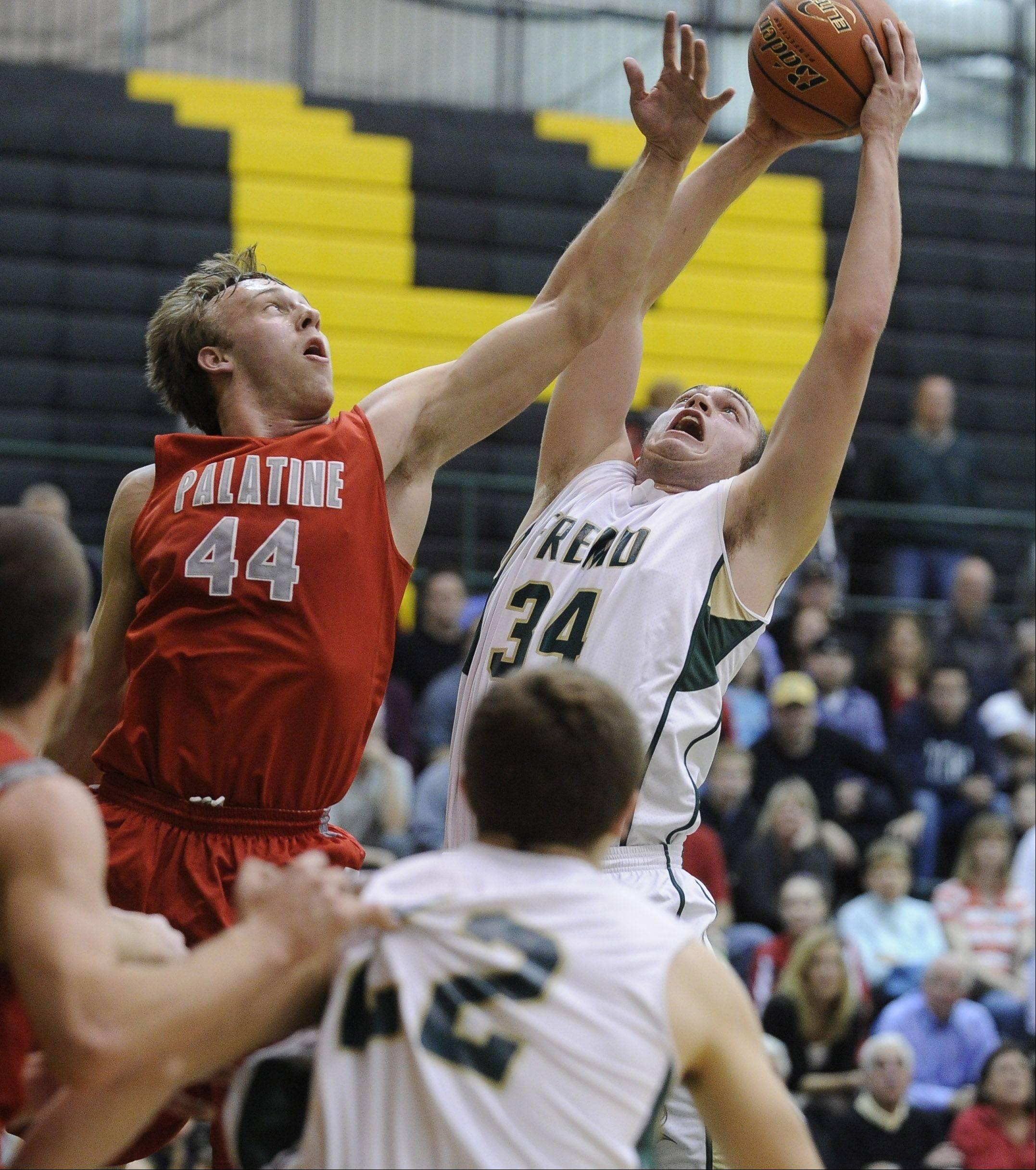 Palatine's Josh Baldus, left, and Fremd's Ben Carlson battle for the rebound in the first half Friday at Fremd.