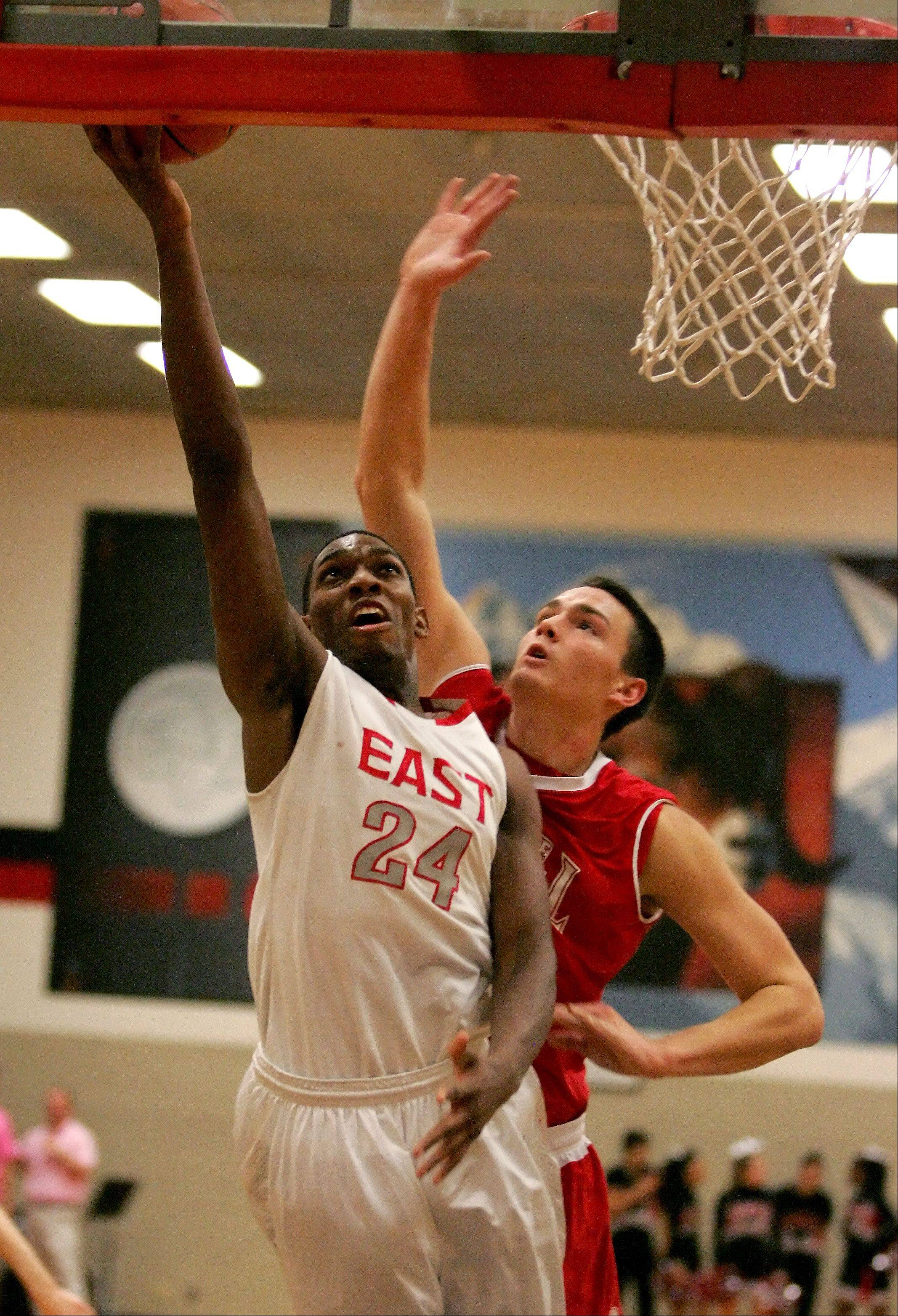 Marvin Grant-Clark, left, of Glenbard East goes up for two points as Nick Czarnowski of Naperville Central defends in boys basketball action Friday in Lombard.