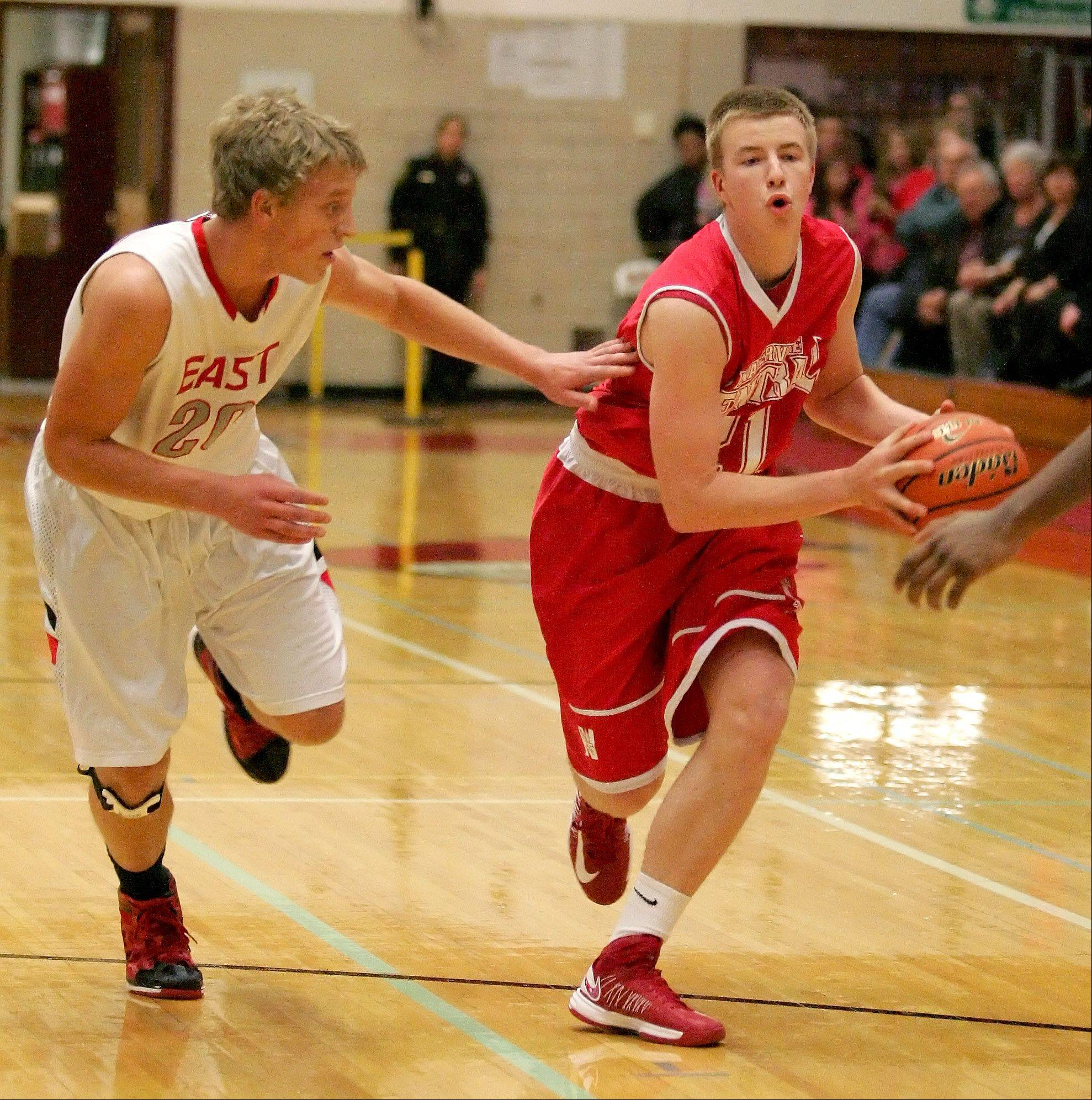 Mike Blaszczyk of Naperville Central, right, keeps the ball from Greg Ludwig of Glenbard East in boys basketball action Friday in Lombard.